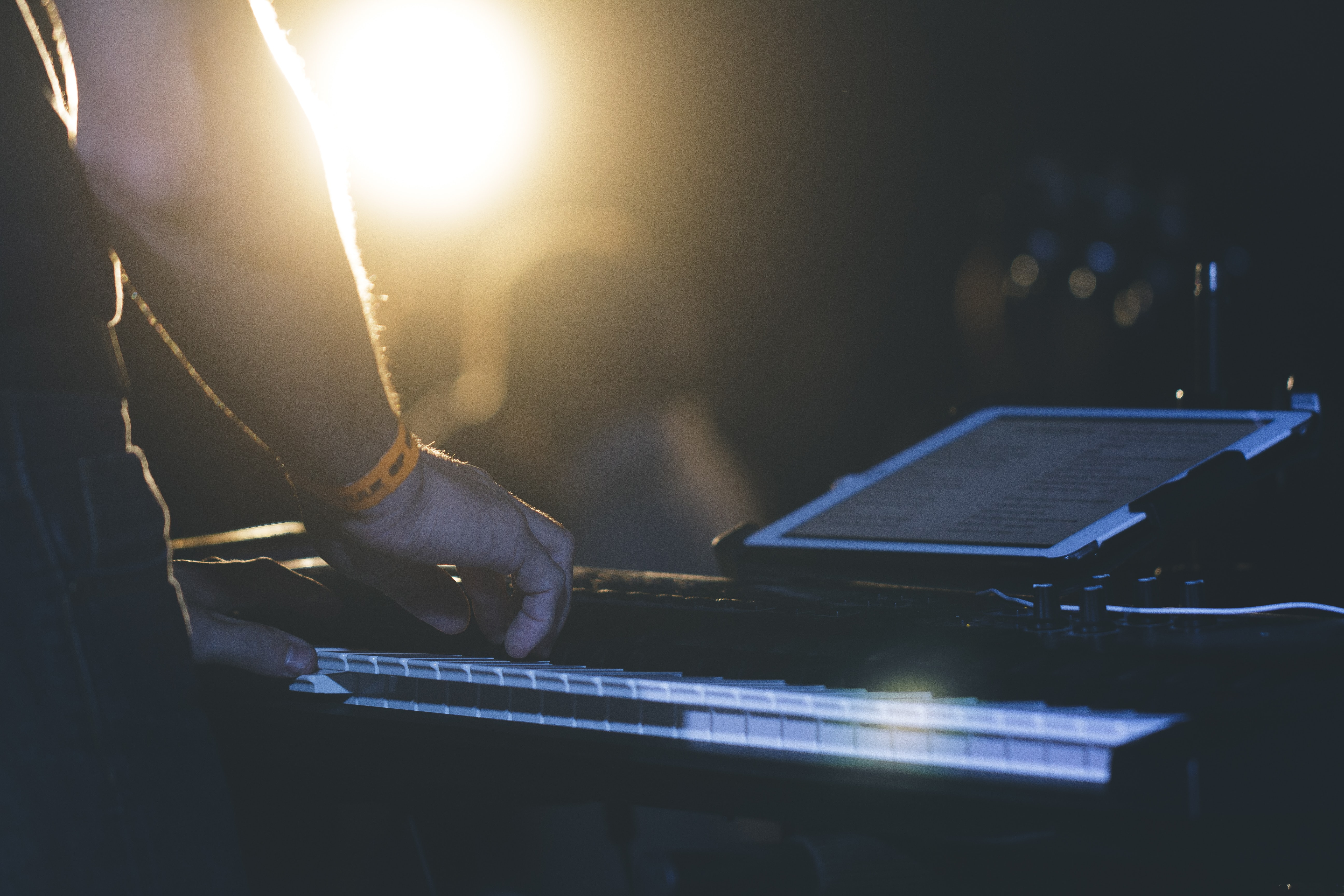 A close-up of a man playing the keyboard with a tablet in front of him
