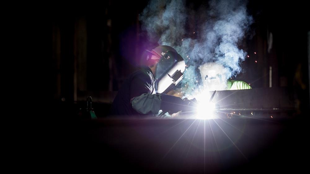 Two people in welding helmets welding in a dark room