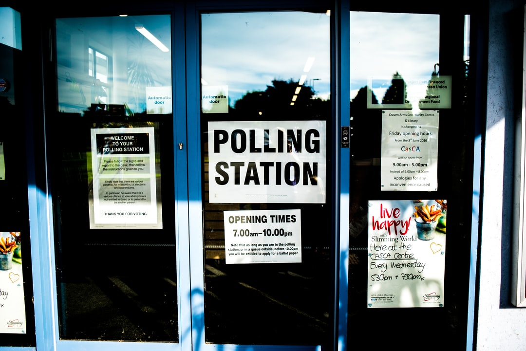 Three reflective glass doors with signs and posters reading Polling Station and Opening Times