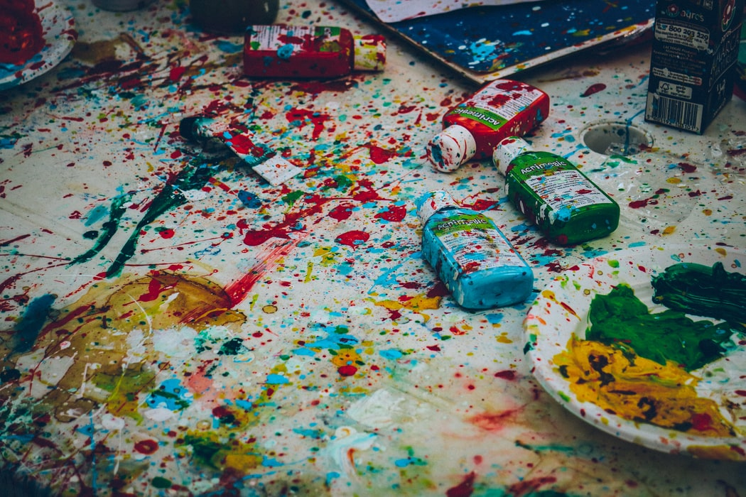 splattered colorful paint on a white table with bottles of paint
