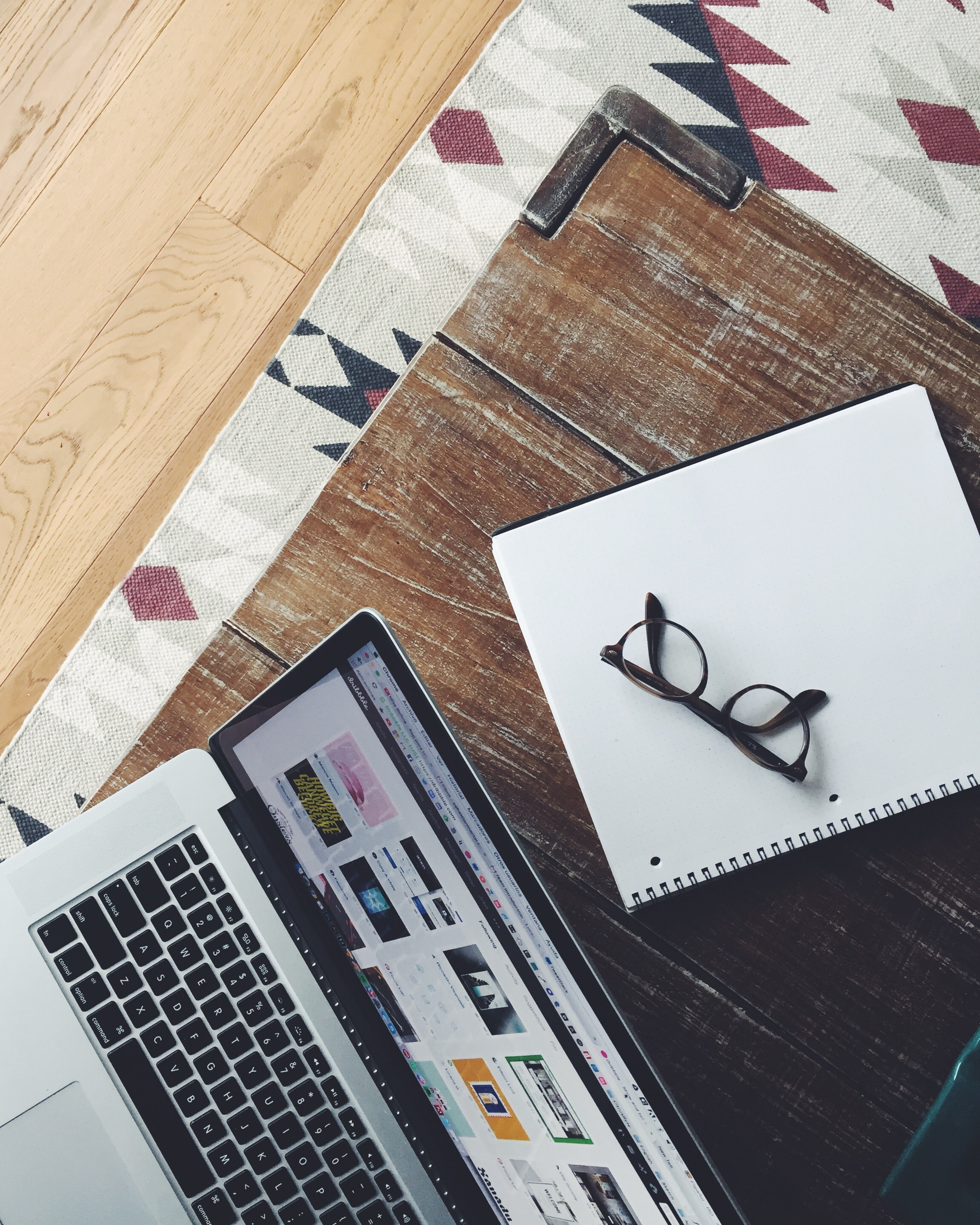 An overhead shot of a pair of glasses on a notebook next to a laptop