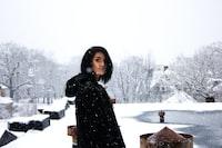 woman wearing black shirt standing under snow weather