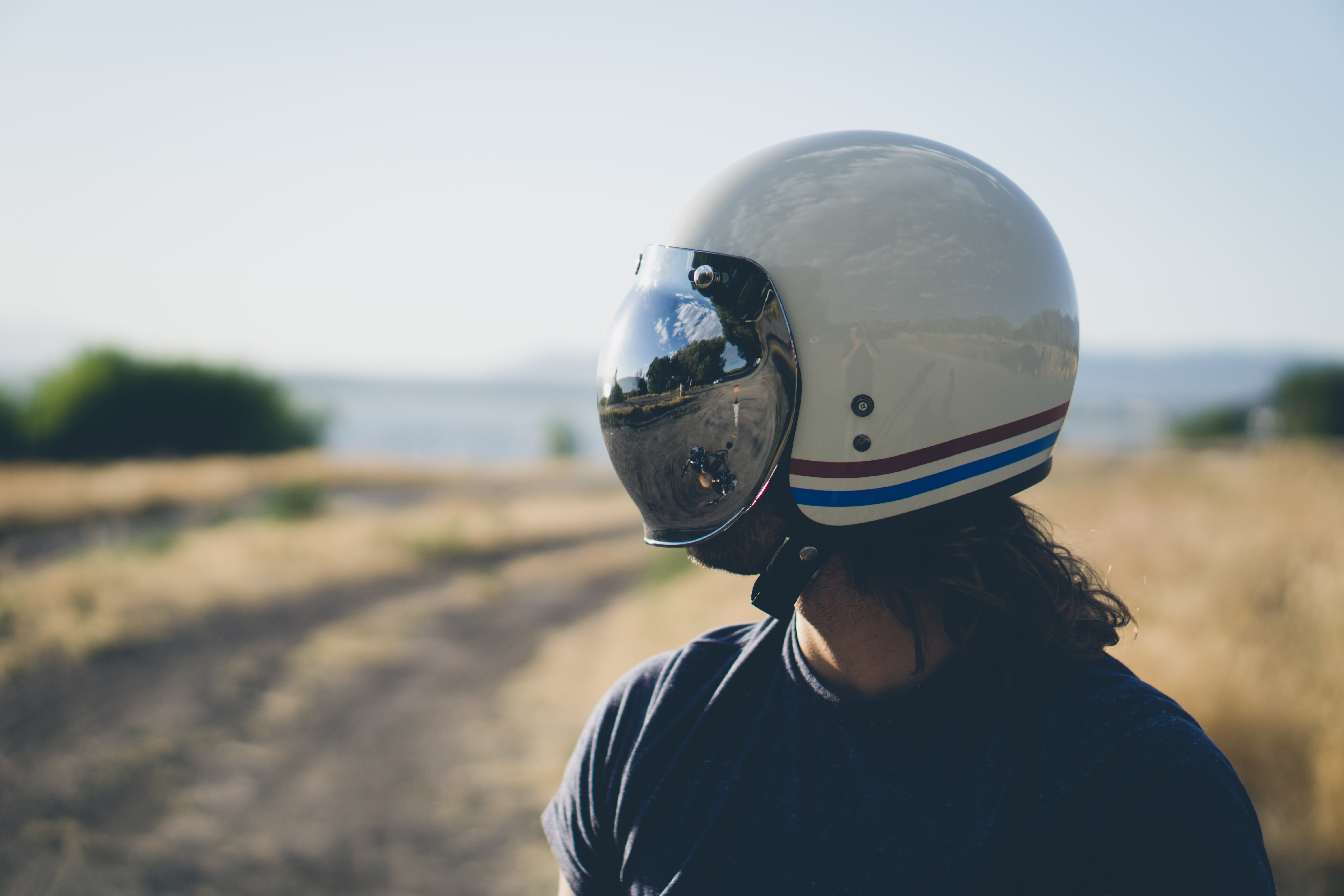 Motorcycle helmet wearing man staring at a field near the water
