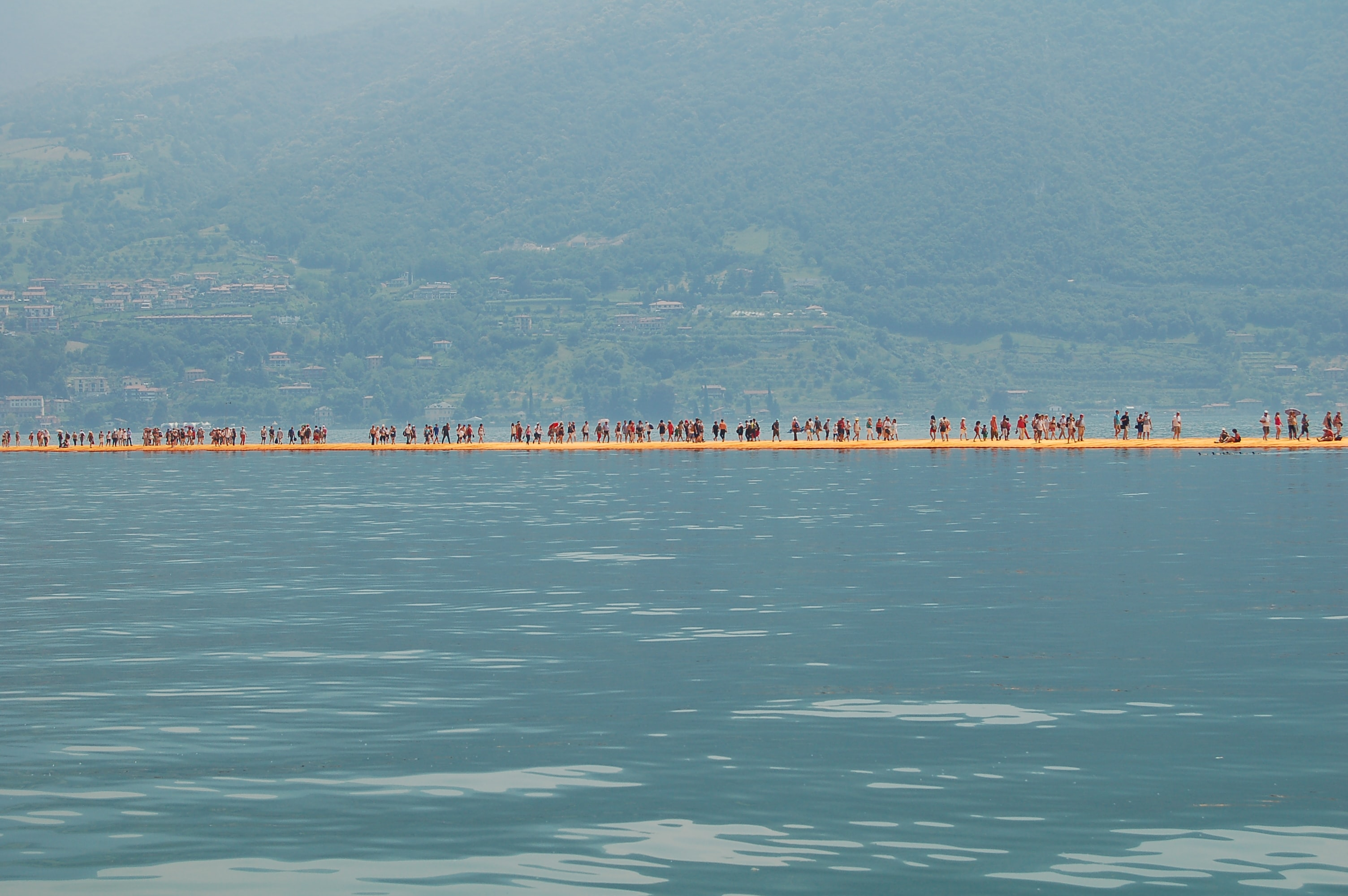 Groups of people standing on the walkway at The Floating Piers with buildings in the distance