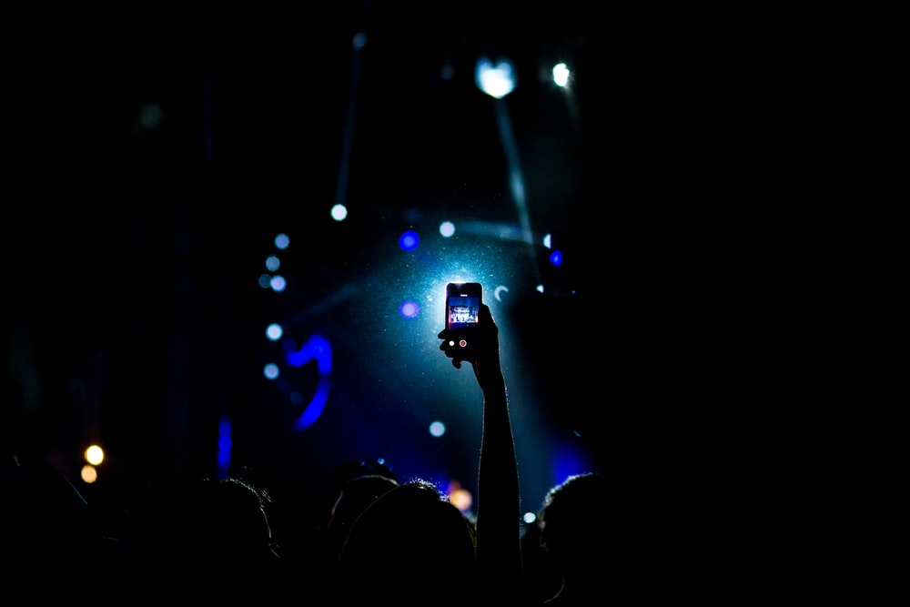 low light photography of person raising hand holding smartphone