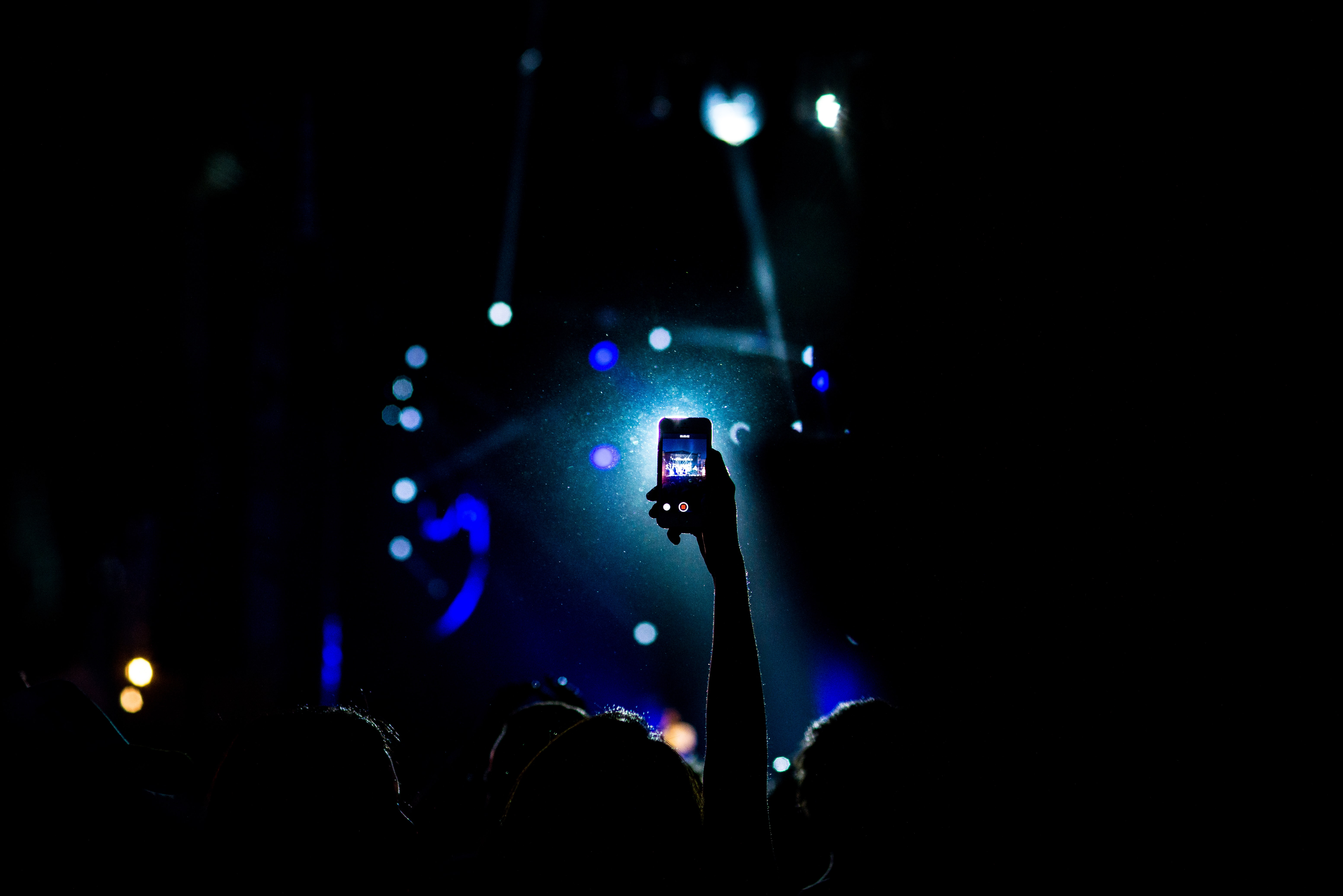 The silhoutte of a person holding up their iPhone cellphone at a concert in Monterrey