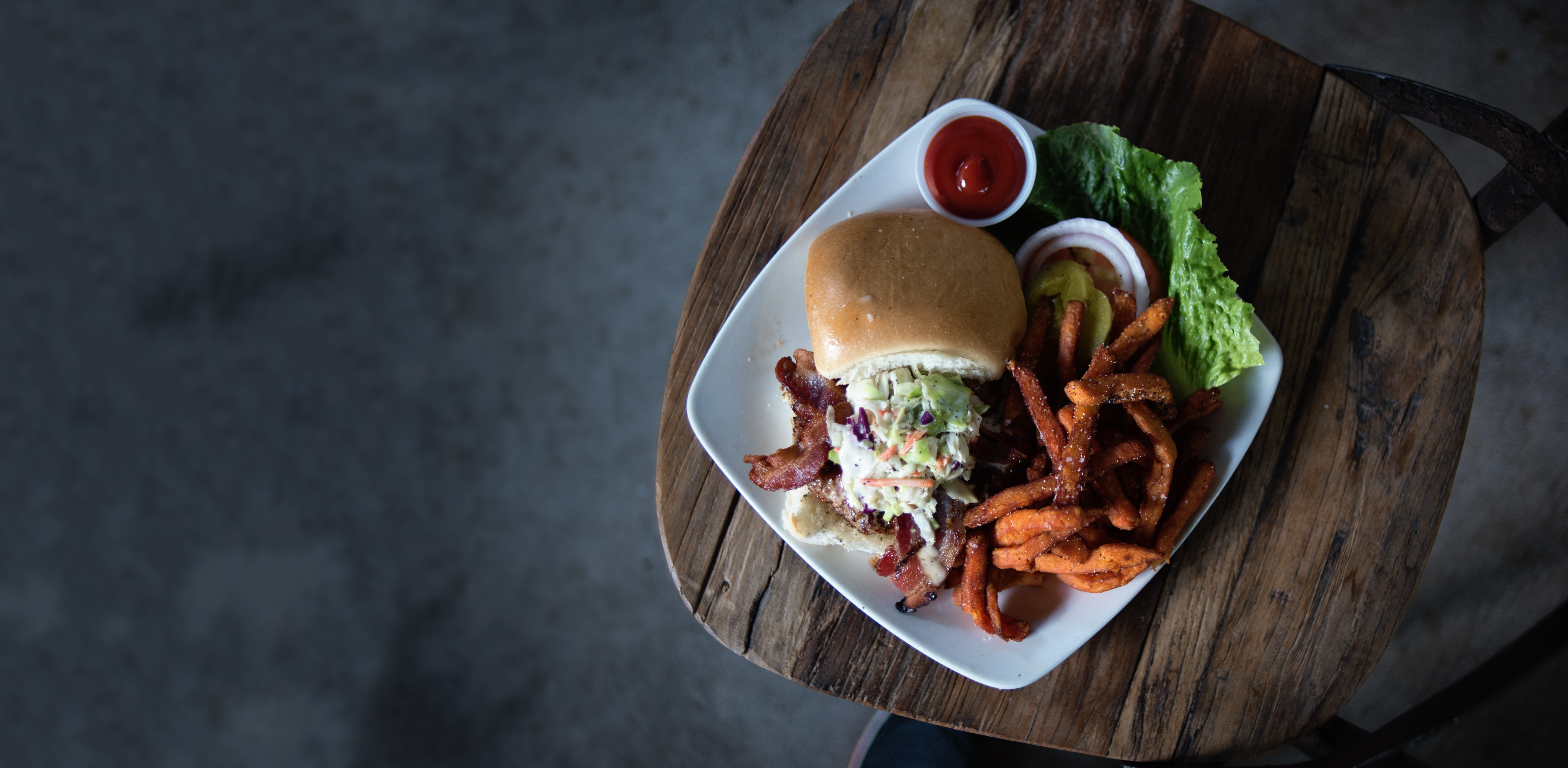 Overhead shot of a loaded burger with sweet potato fries