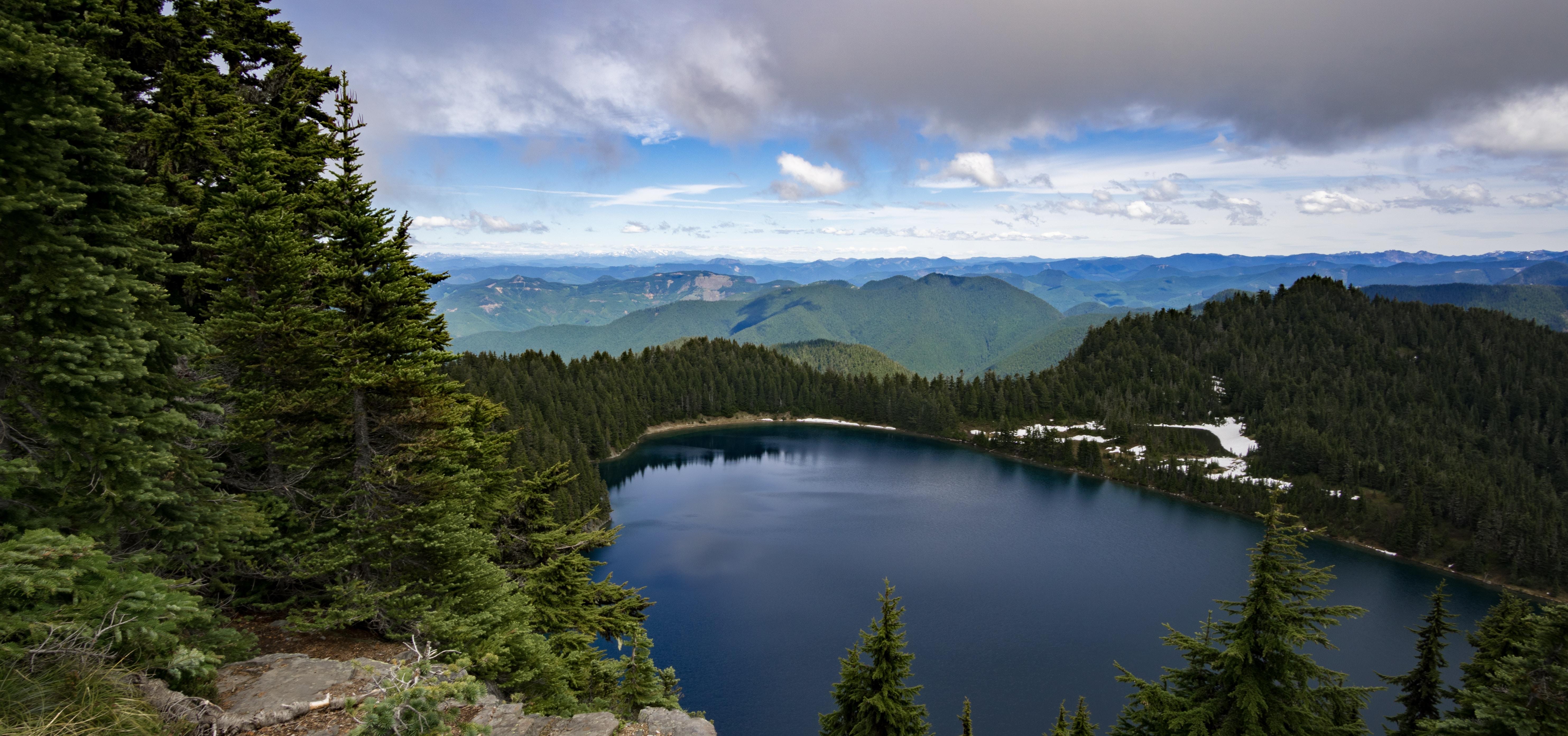A smooth dark lake among green hills