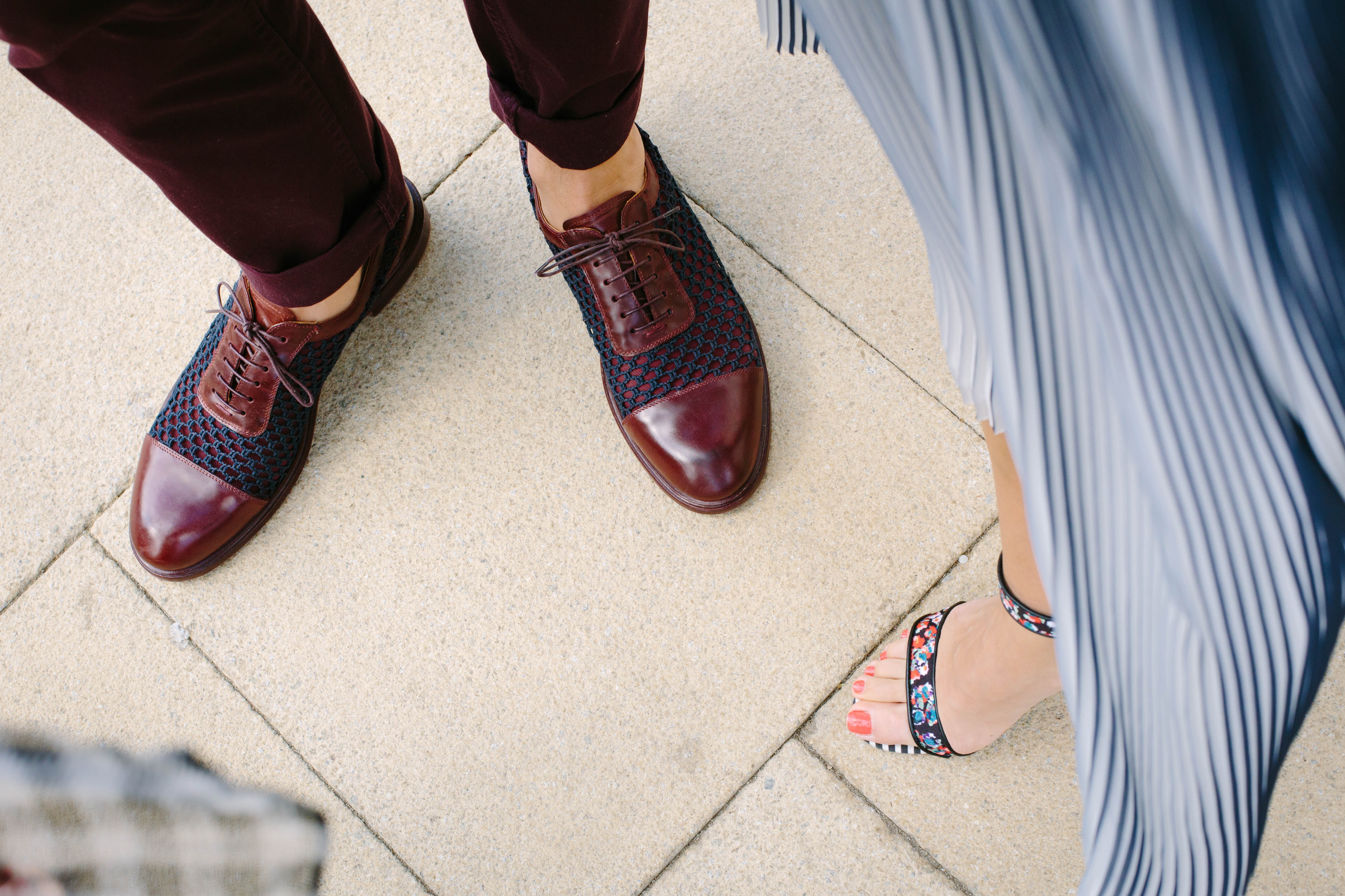 A man in brown leather shoes next to a woman in stylish sandals