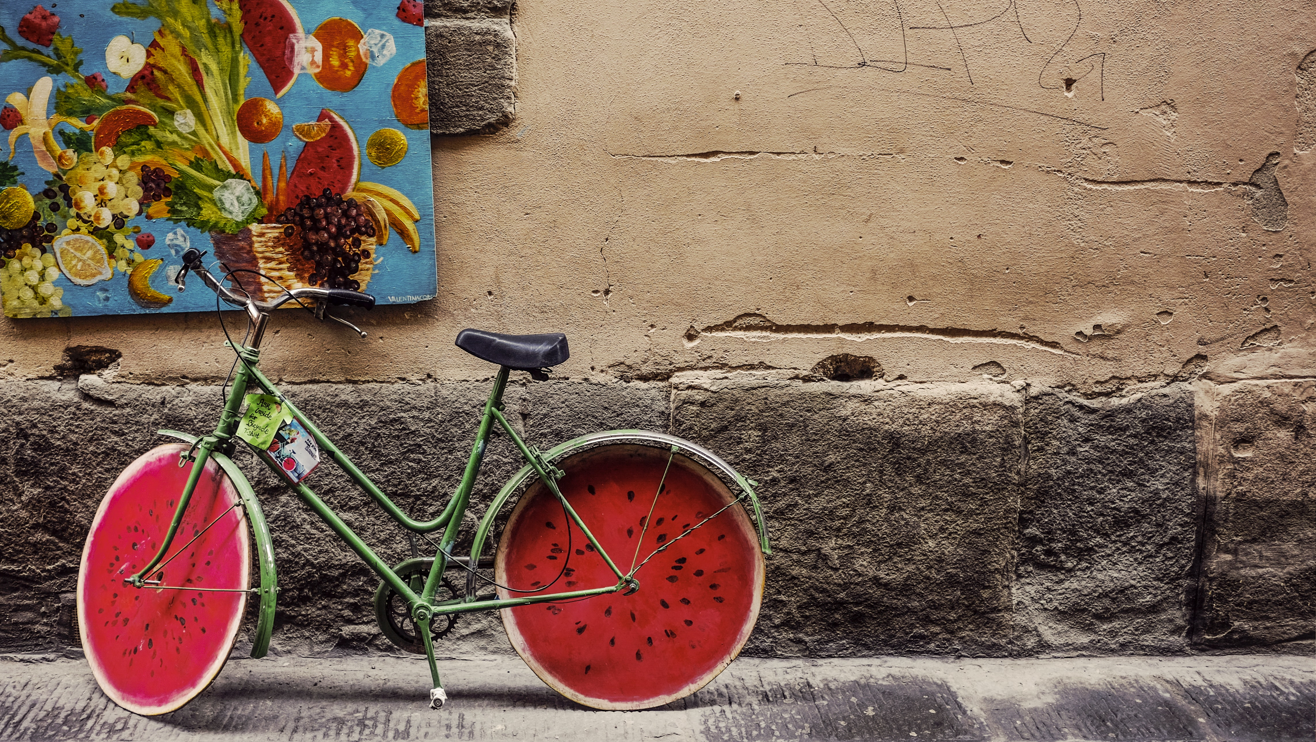 A green bicycle with wheels resembling a cross-section of a watermelon