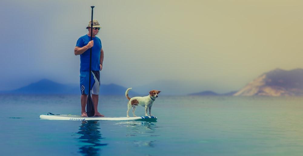 man wearing blue shirt standing on white surfboard