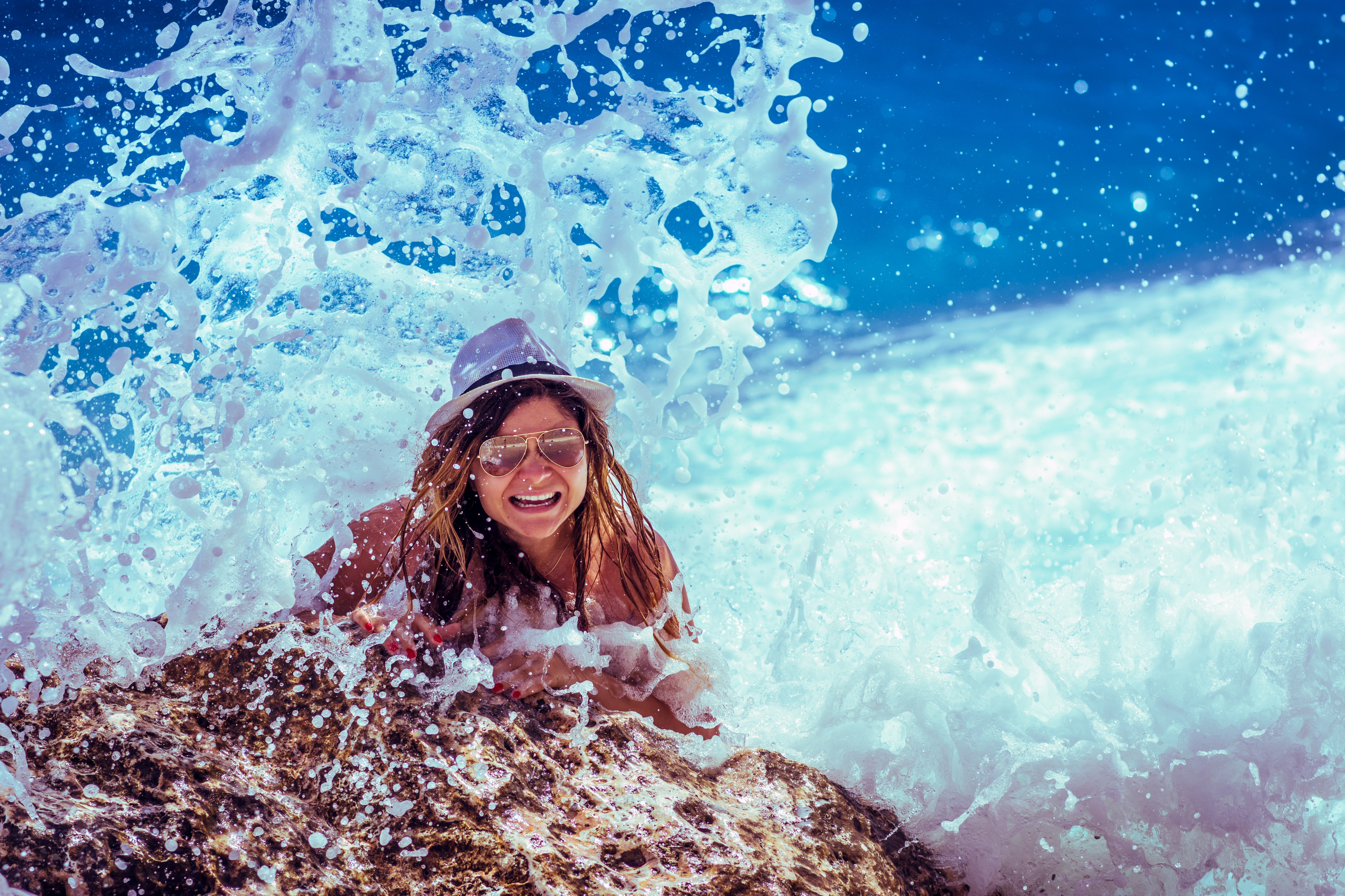 A girl wearing a hat hanging on rock being hit by a wave from the ocean at Lalaria beach