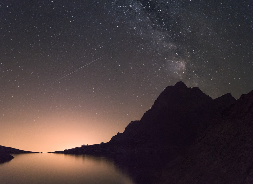 silhouette of mountain beside the body of water at night time