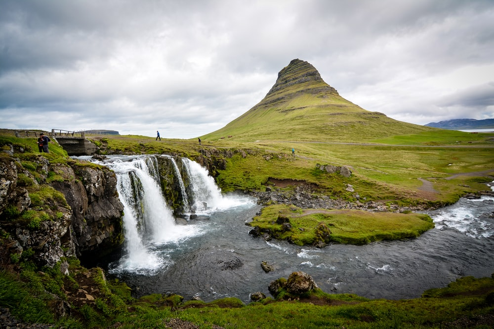 photo of waterfalls beside hill during cloudy daytime