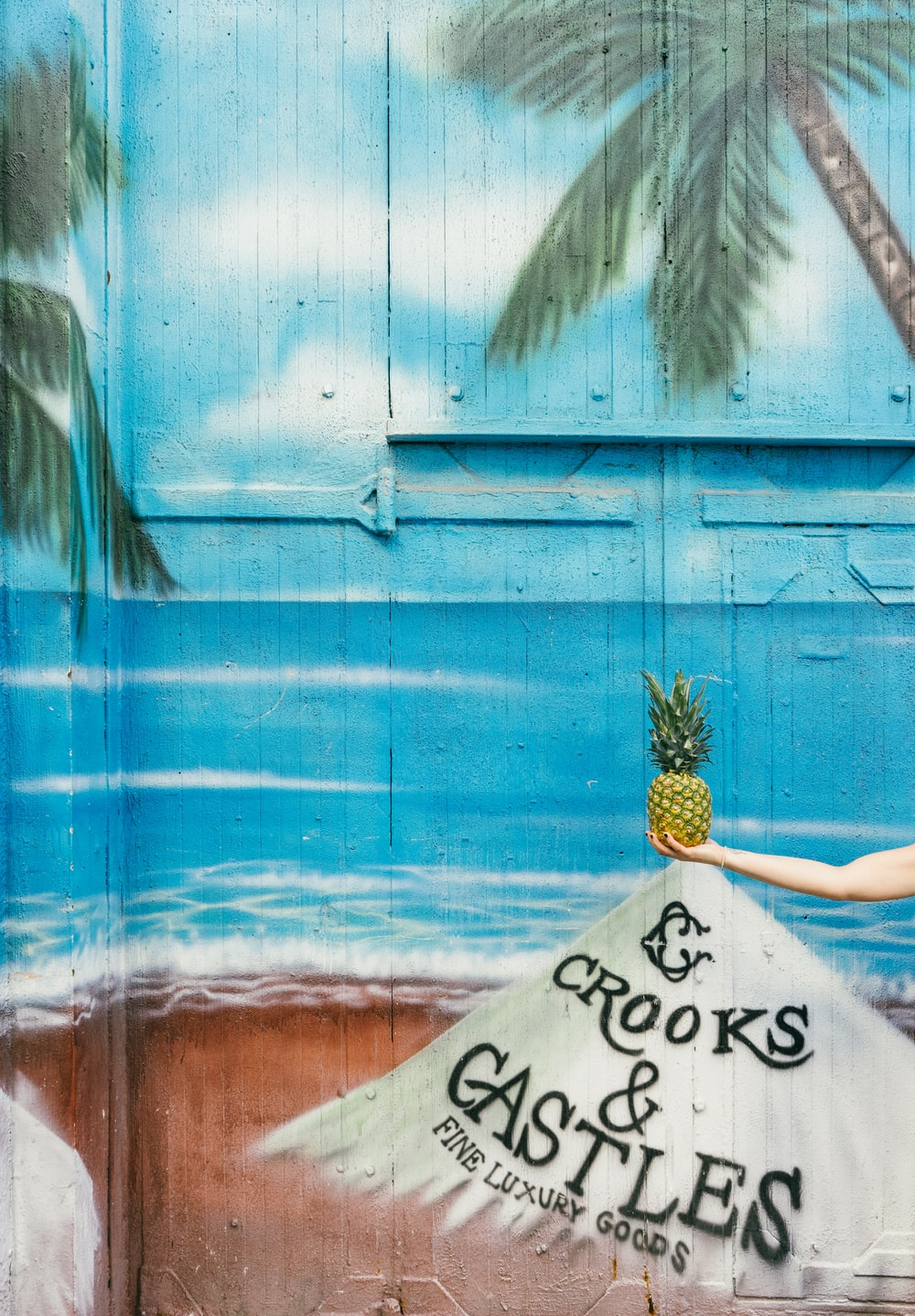Mural painting of a pineapple on the beach.