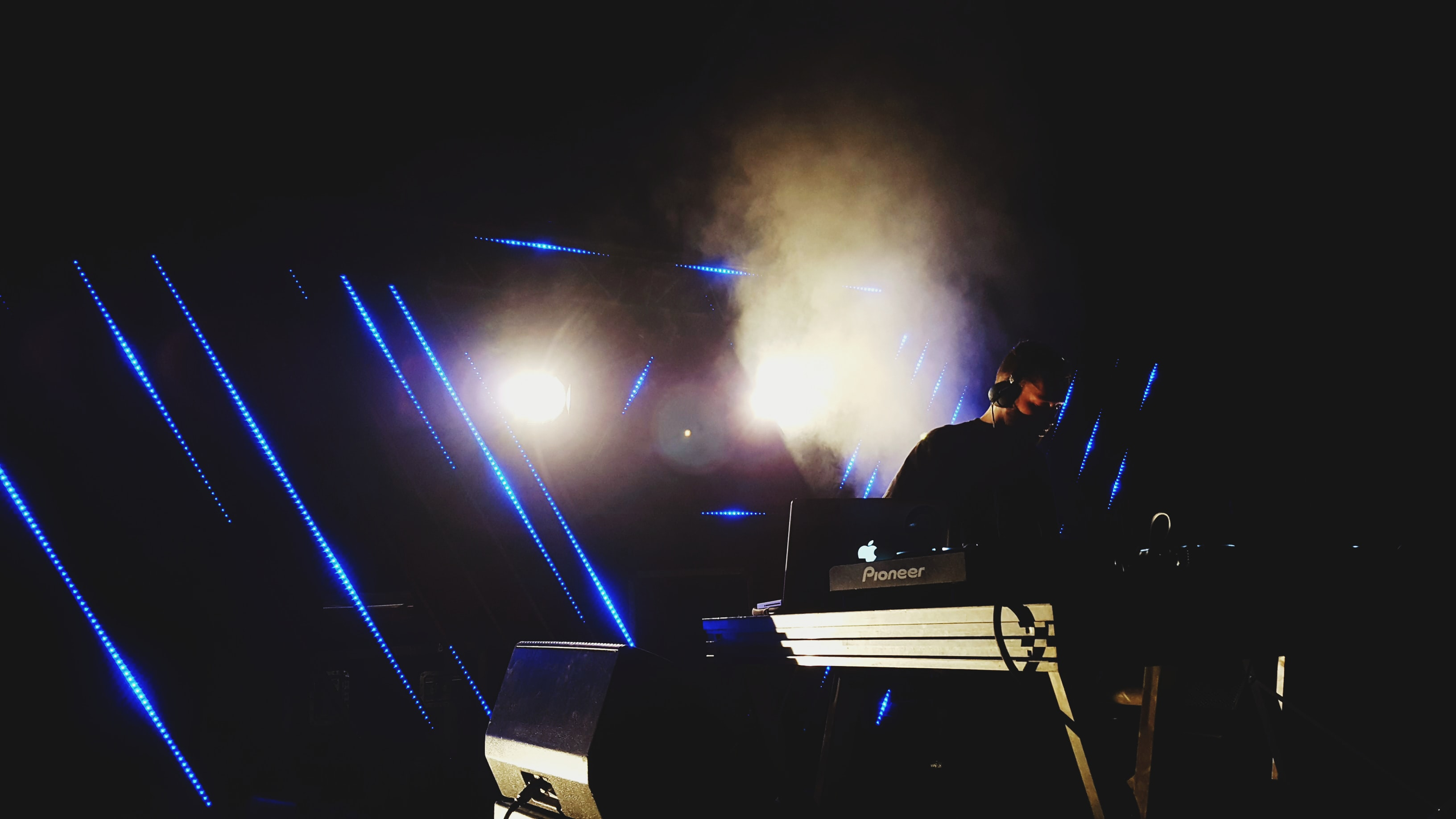 A male DJ performing in a dark club with pale blue lights behind him