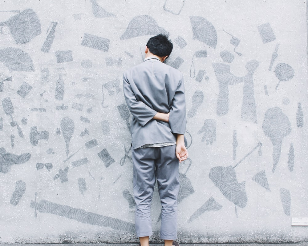 Man wearing gray suit leans face-first against gray wall with art