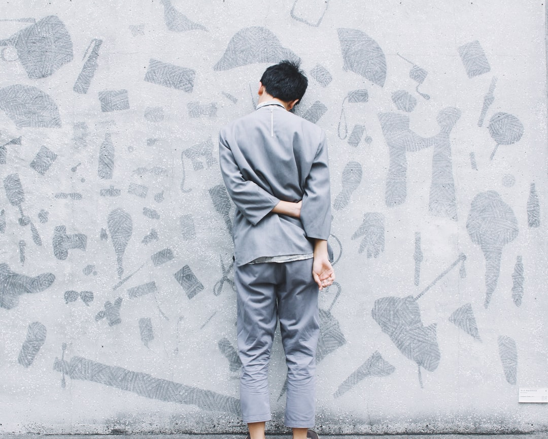 Man leans against gray wall