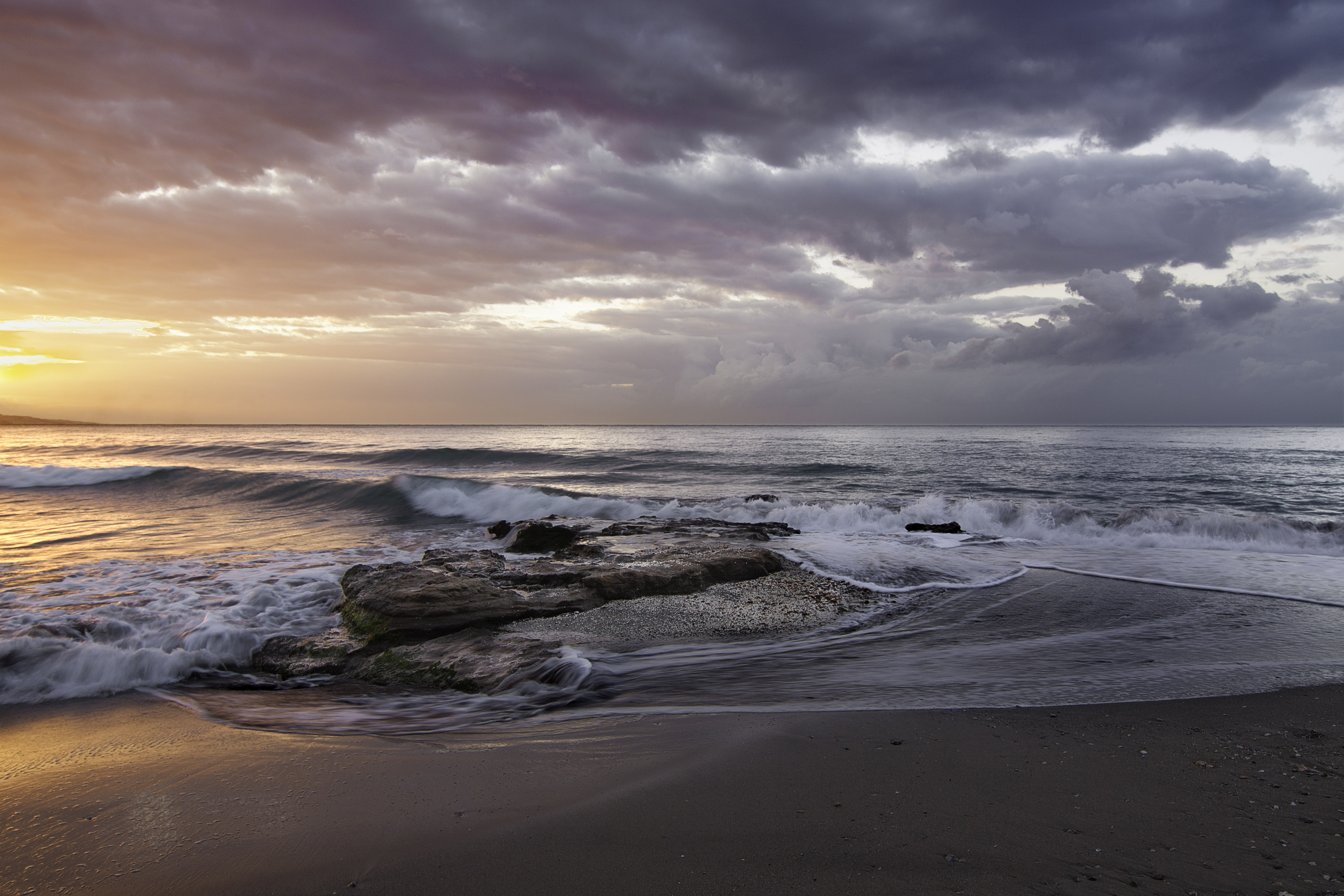 Overlapping waves on a beach with a stormy orange and grey sky at sunset.