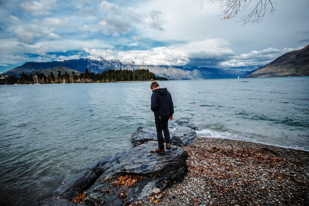 man standing on seashore under cloudy sky
