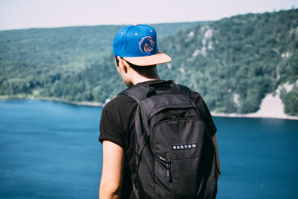 man wearing black t-shirt, black backpack, and blue fitted cap facing body of water photo
