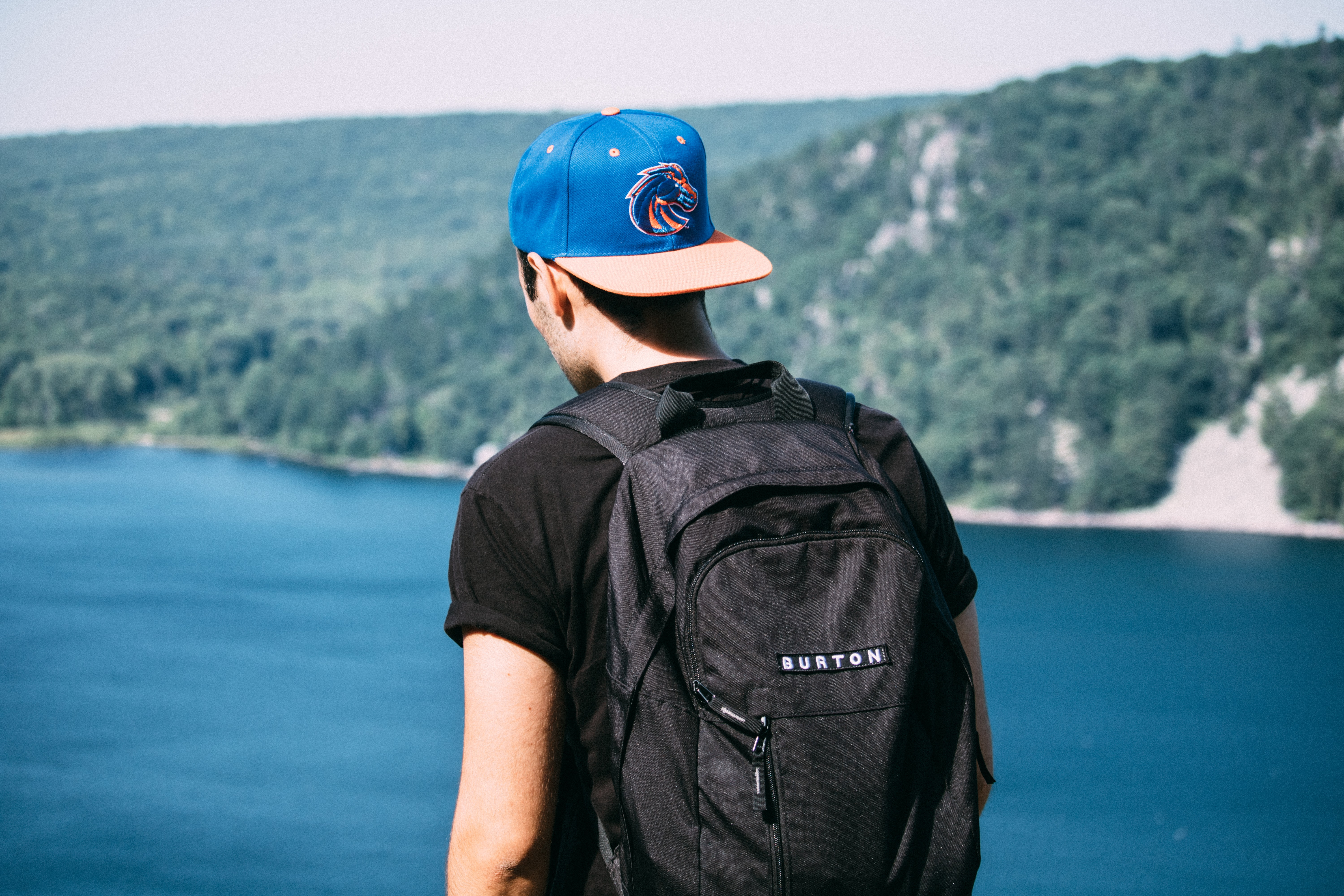 The back of a man wearing a backpack and cap backwards looking out in devil's lake by forest of trees