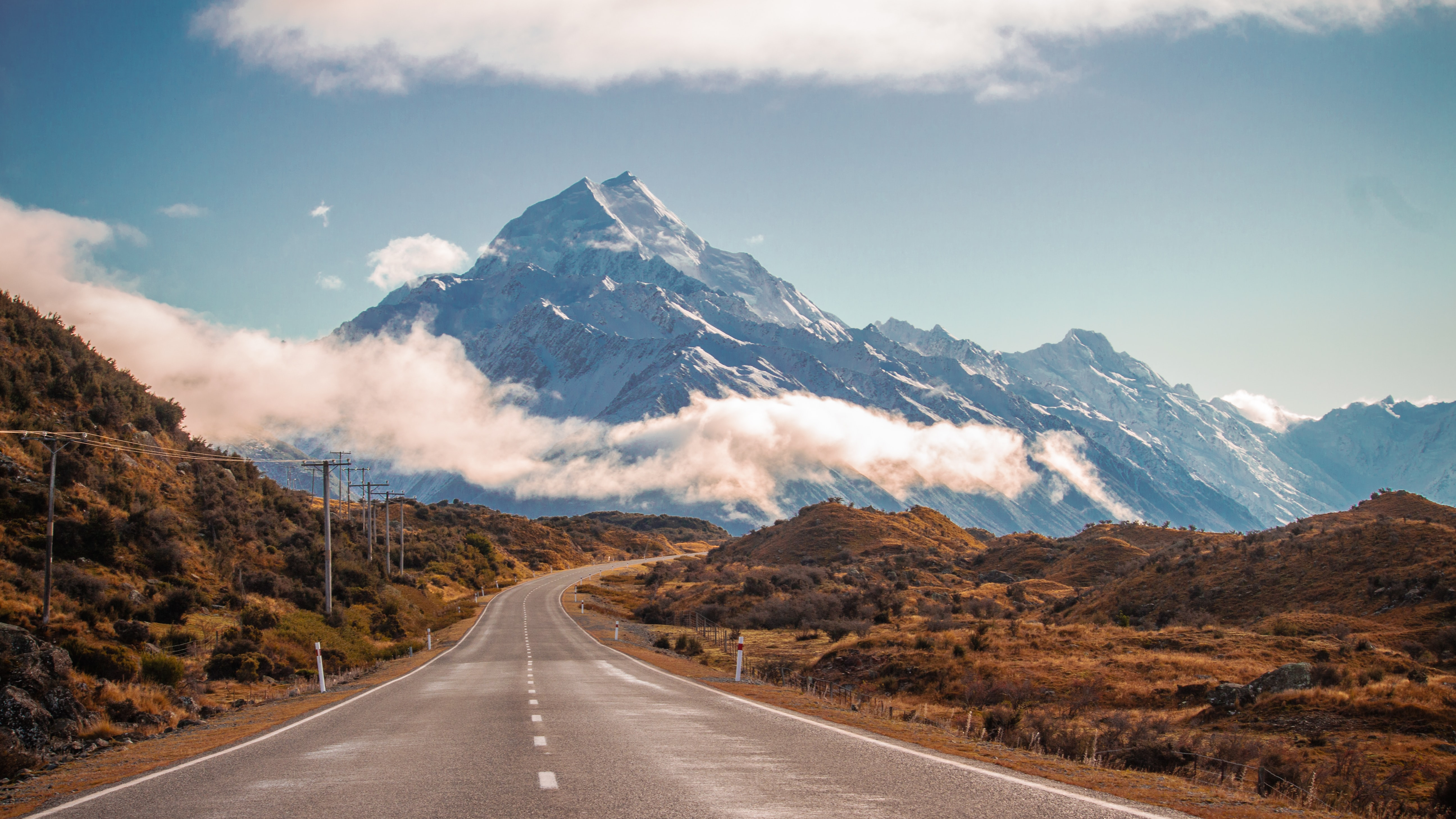 An empty bending road near the towering Mount Cook