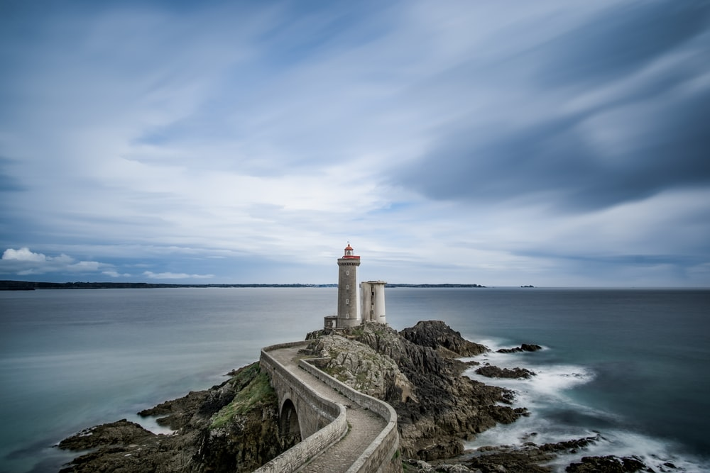 grey concrete lighthouse on cliff surrounded body of water during daytime