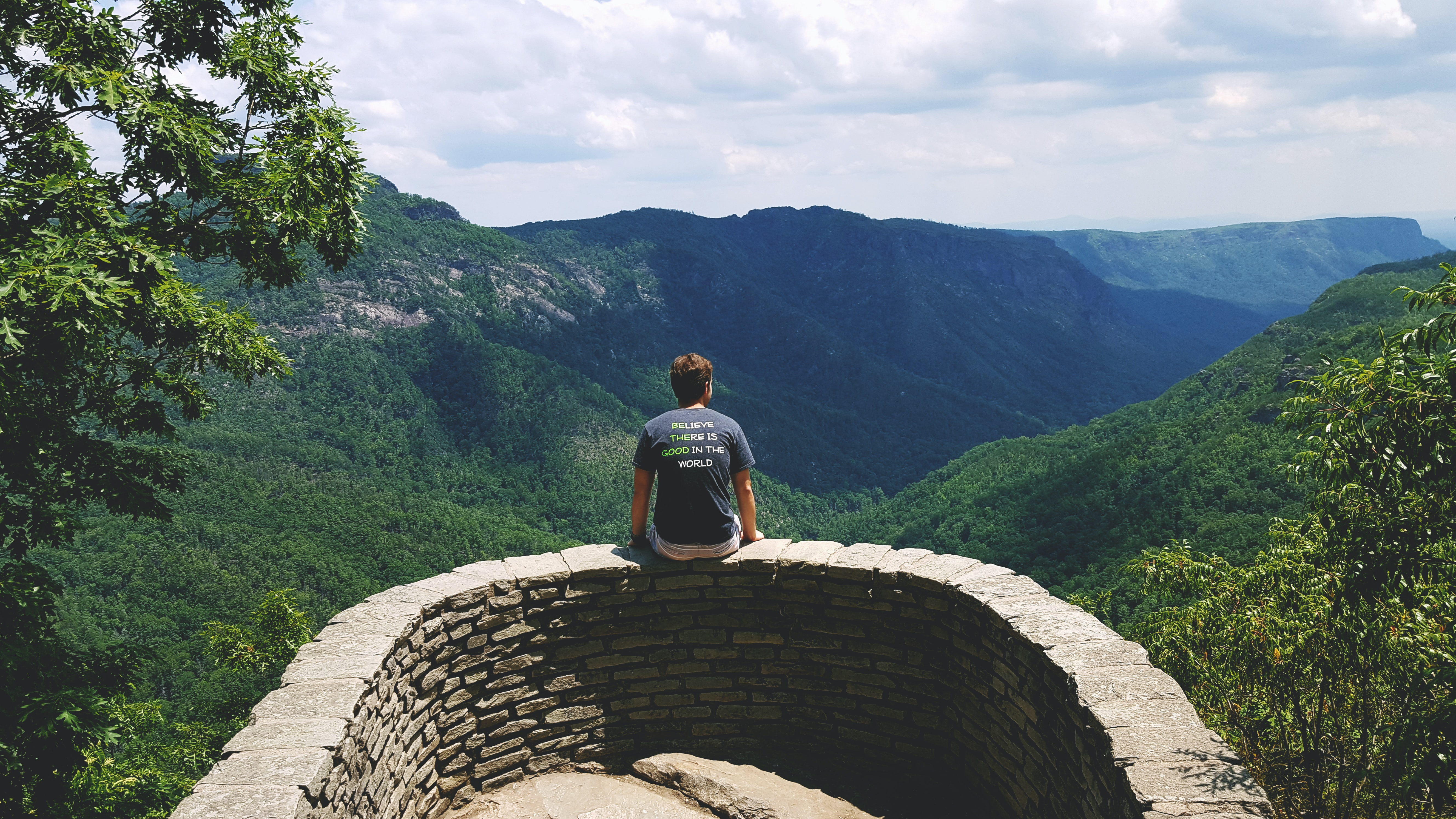 A man sitting on a small stone wall overlooking a green mountain valley