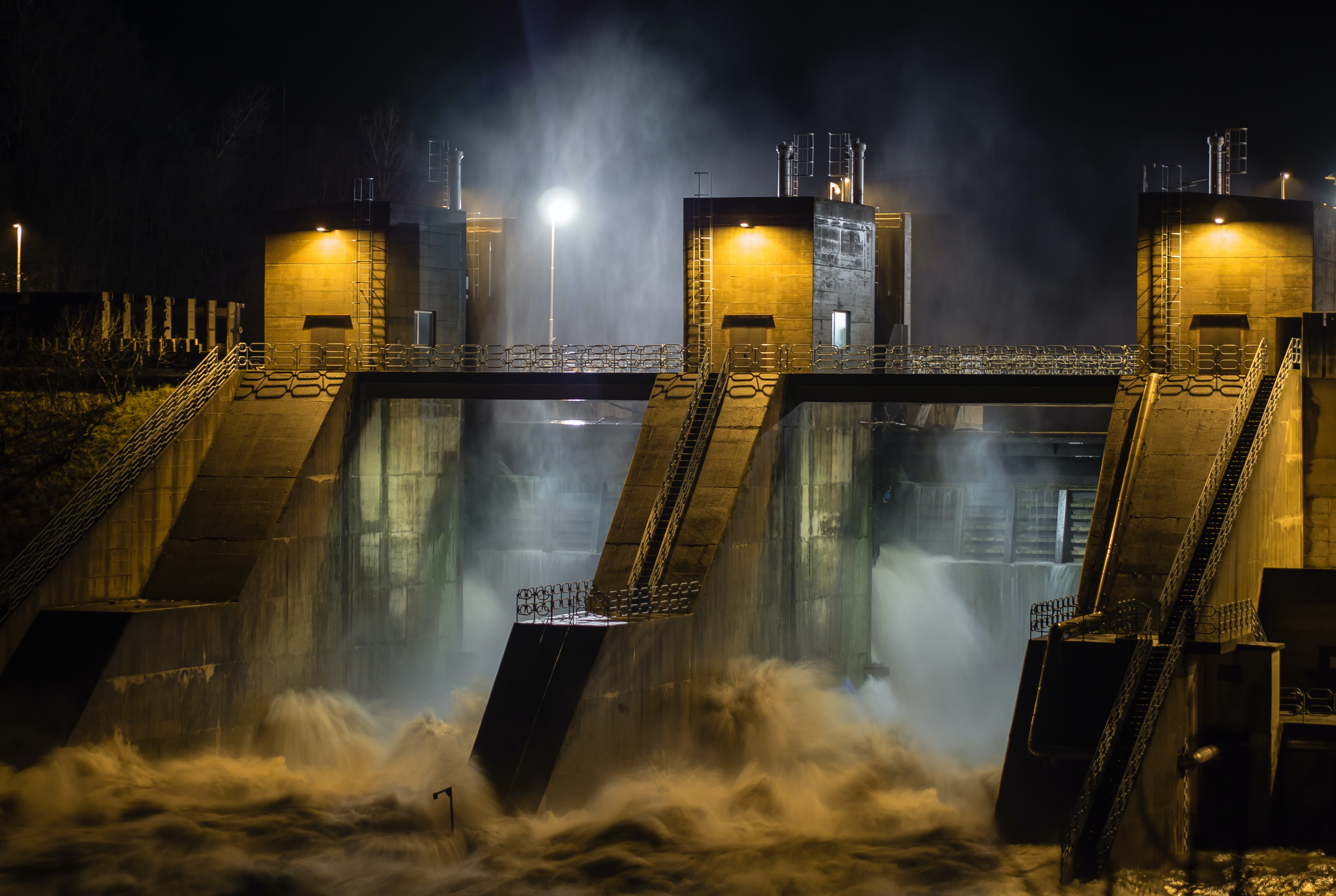 Industrial hydroplant buildings with rushing water on a dark stormy night