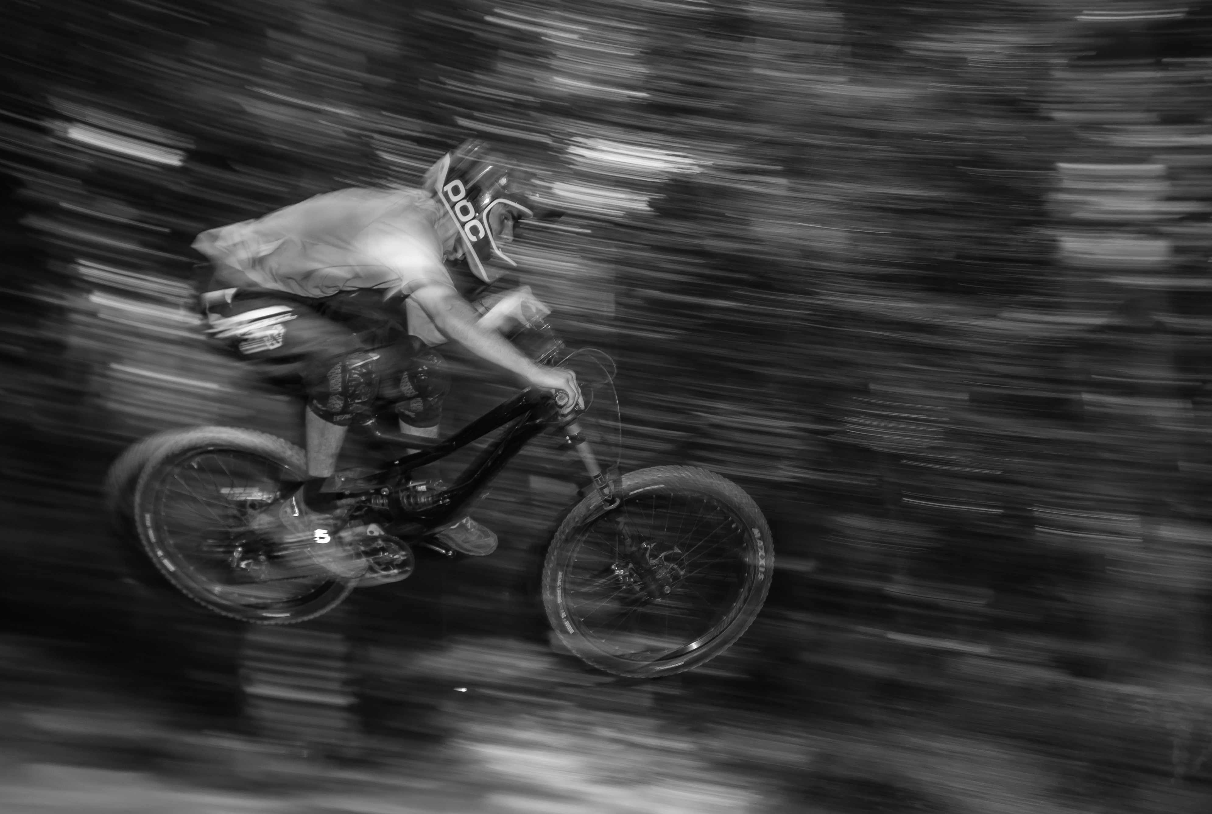 A mountain biker wearing a helmet and knee pads jumping through the air on his bike