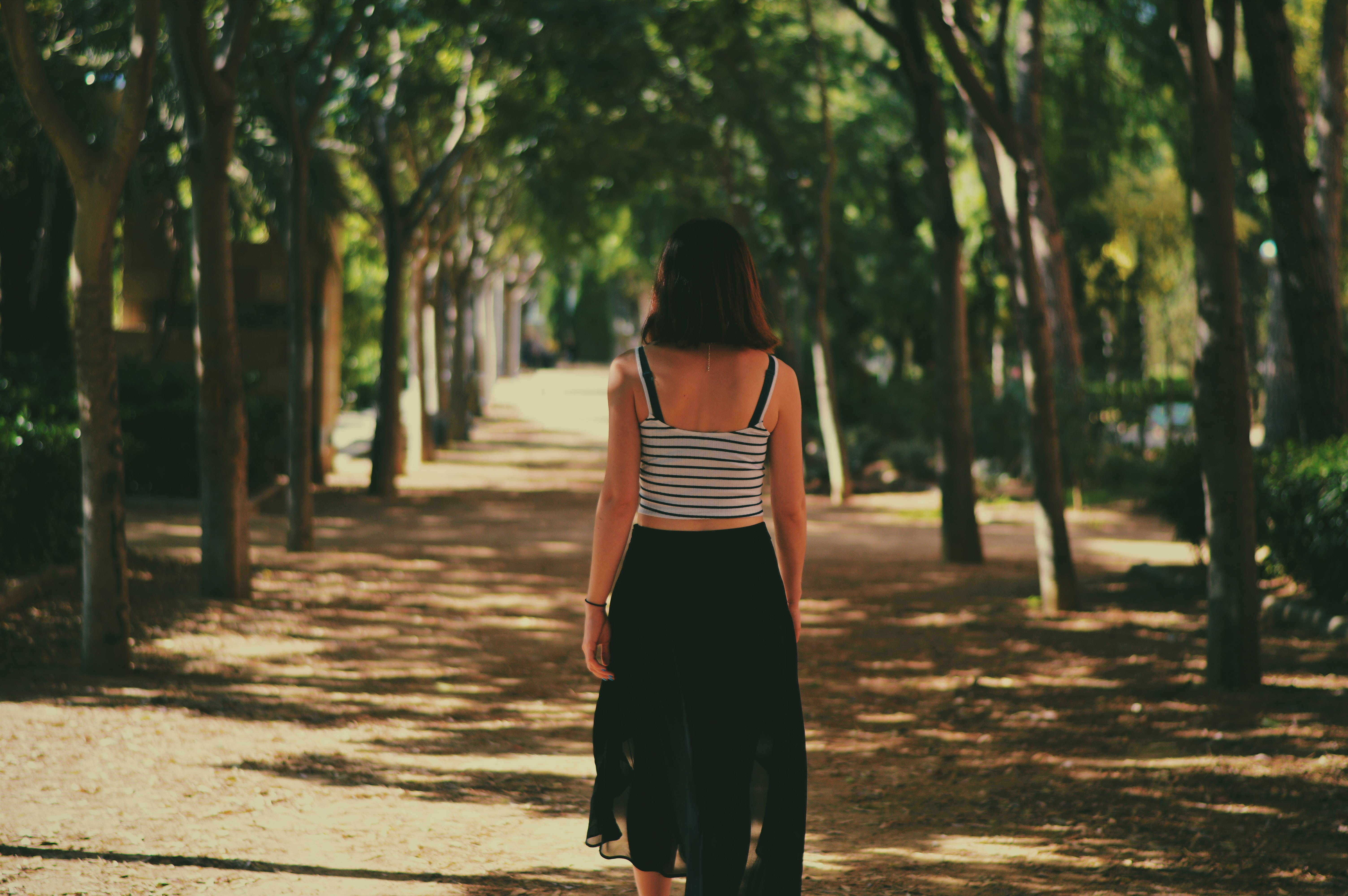 A woman in a striped tank top and black skirt walks away down a tree-lined path