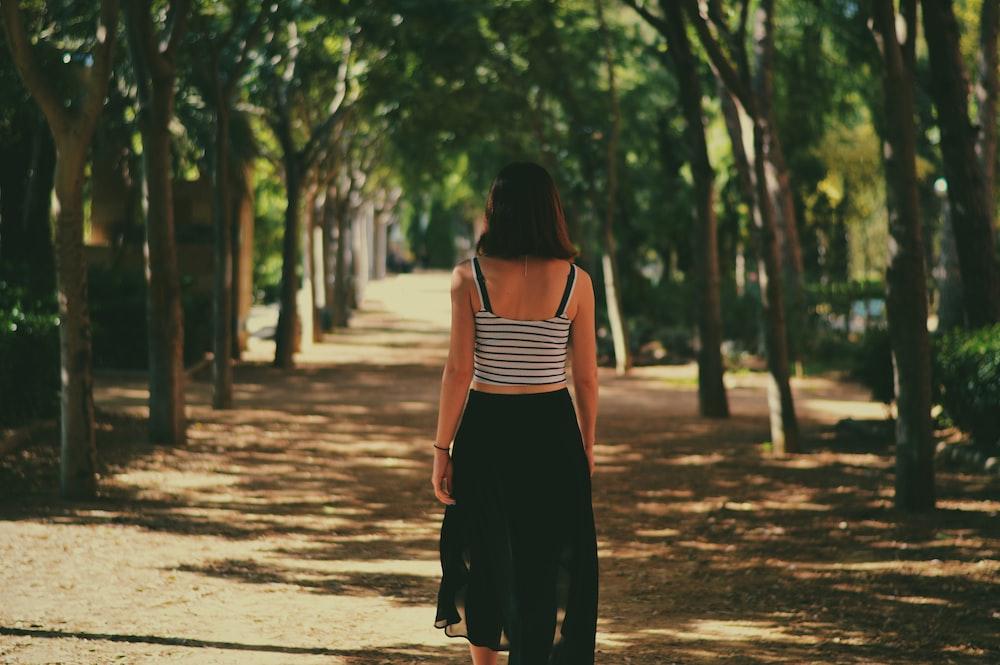 woman walking in between trees