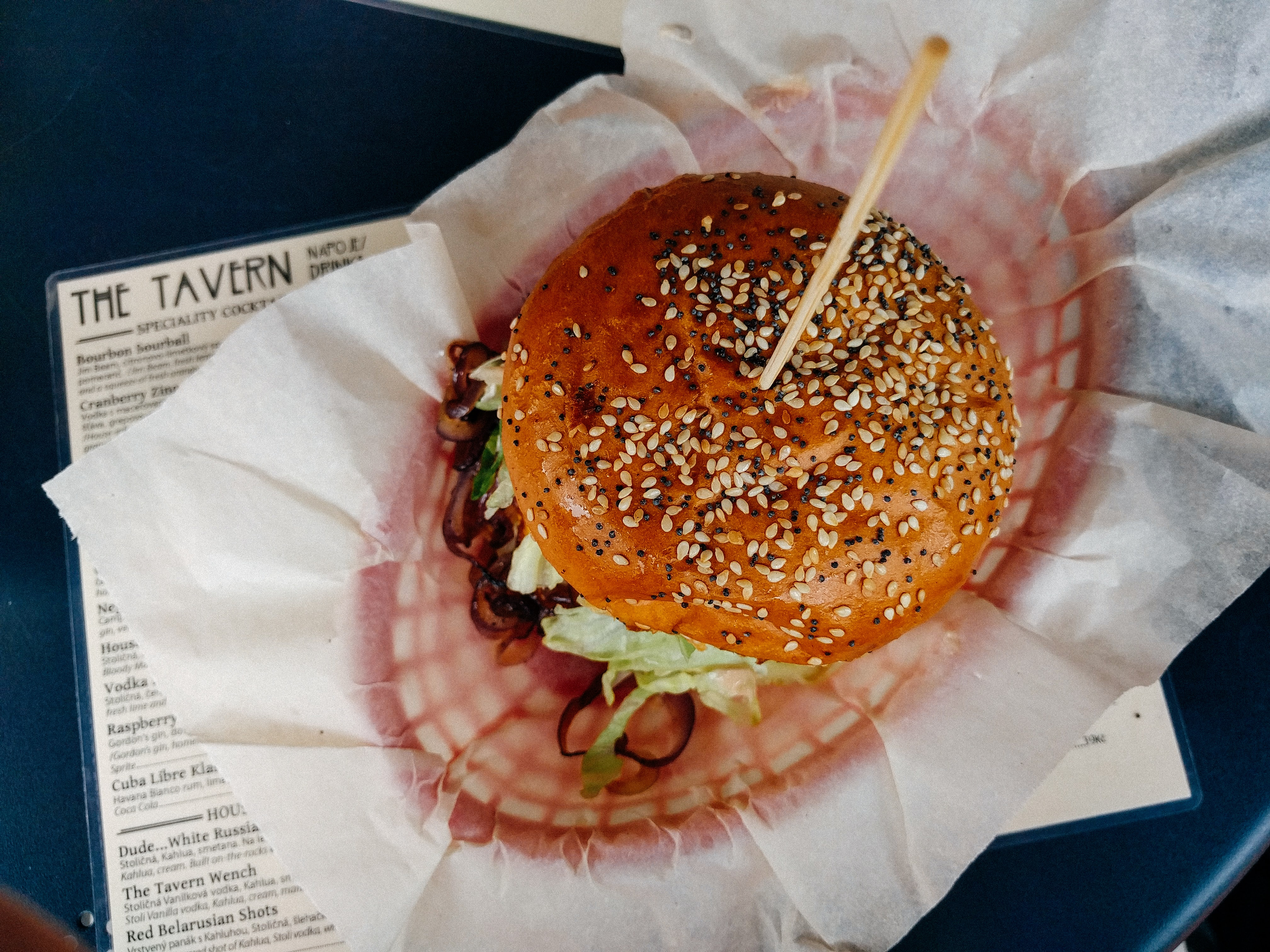 Burger with a sesame seed bun at a bar and grill restaurant