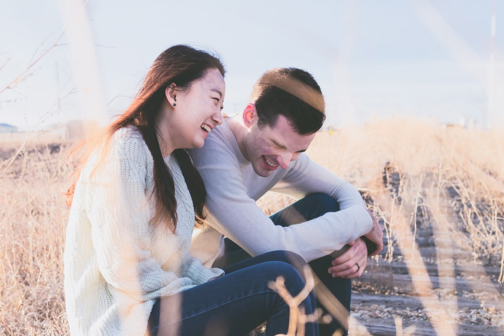 photo of man and woman laughing during daytime