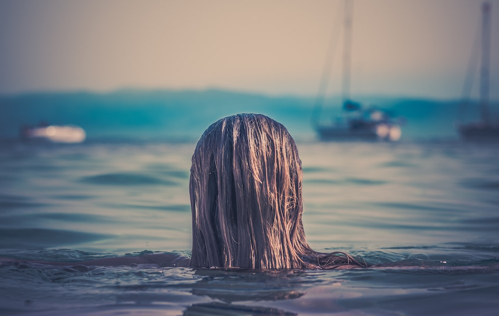 Woman's long hair head above the water at Banana Beach
