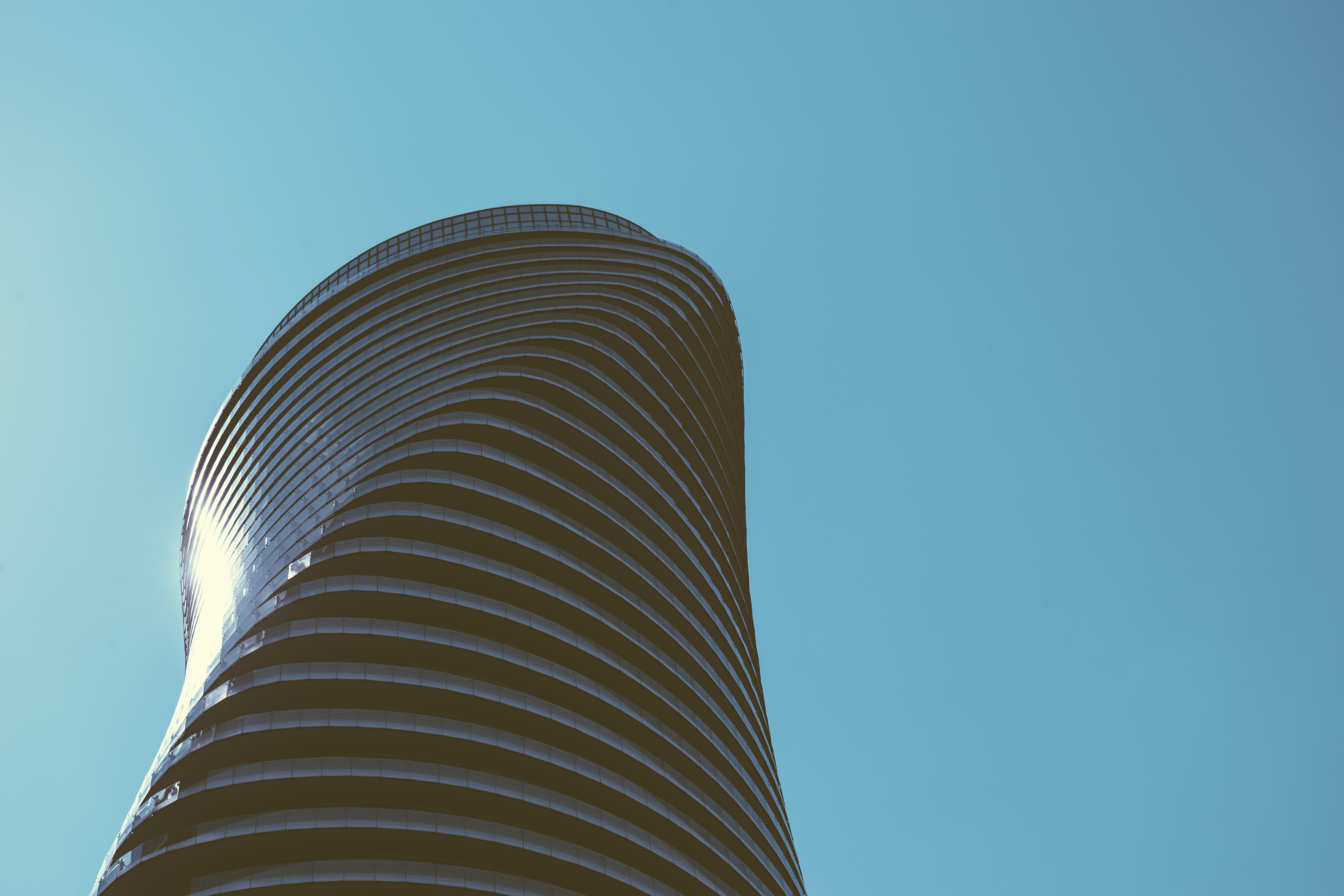 Sun reflected in the curved facade of a postmodern skyscraper