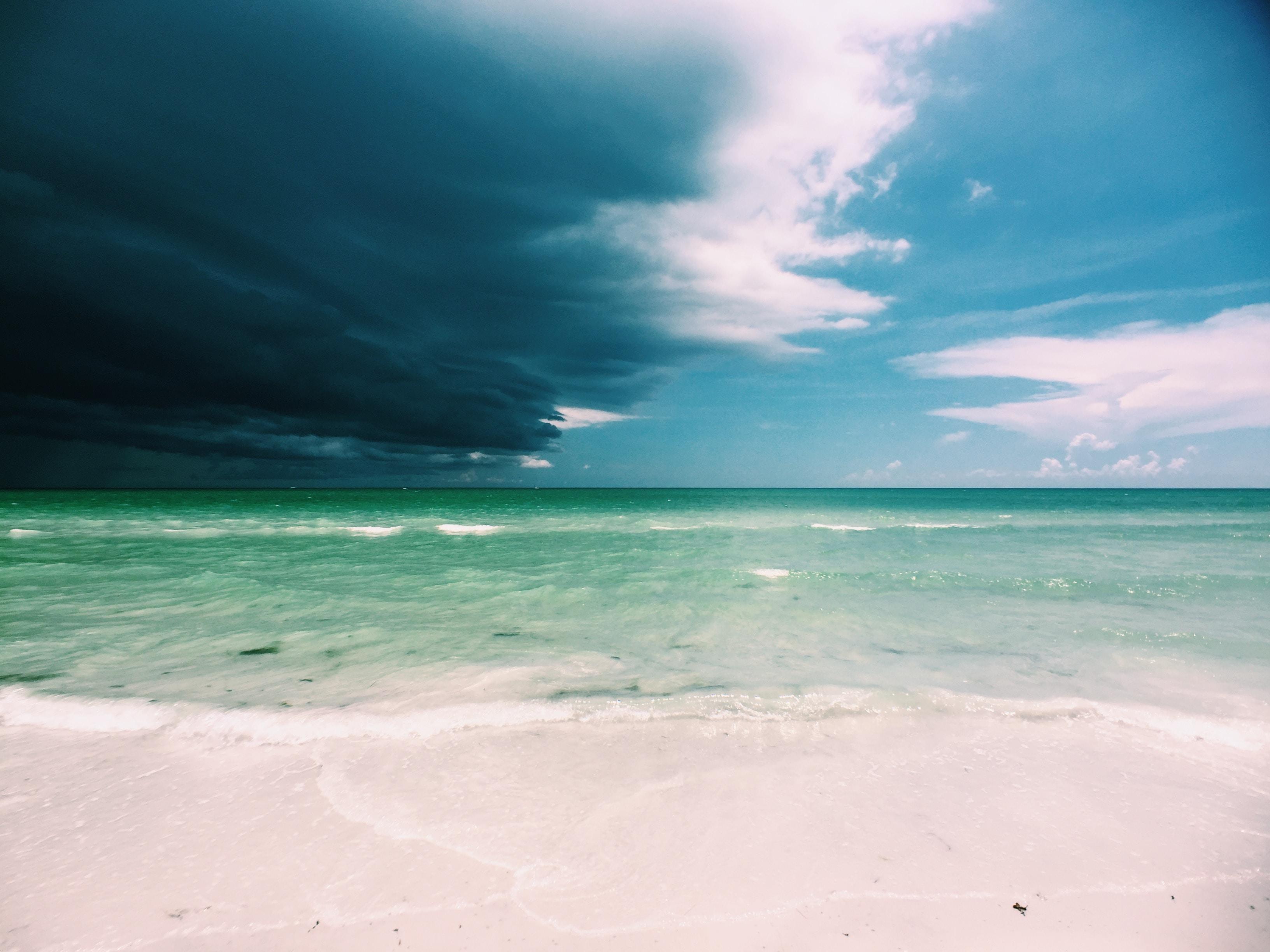 clear white sand beach under cloudy sky