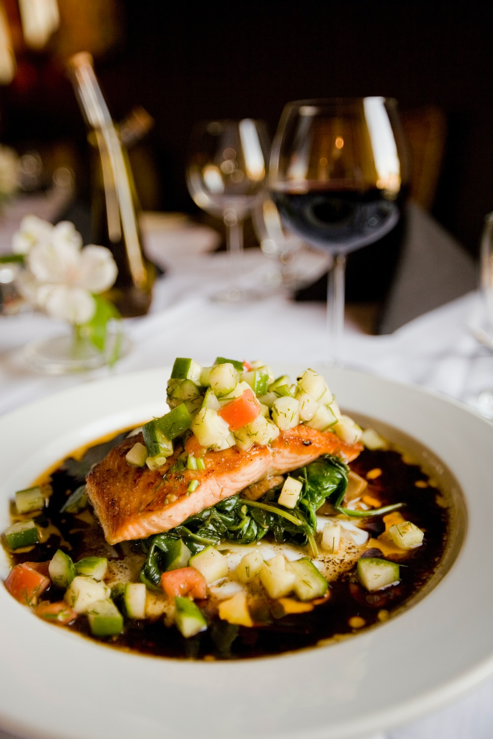 A deep dish with a meal with salmon and zucchini next to a wine glass on a white tablecloth
