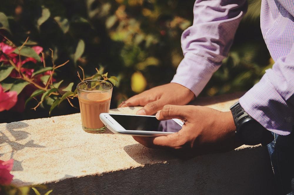 man using smartphone beside drinking glass