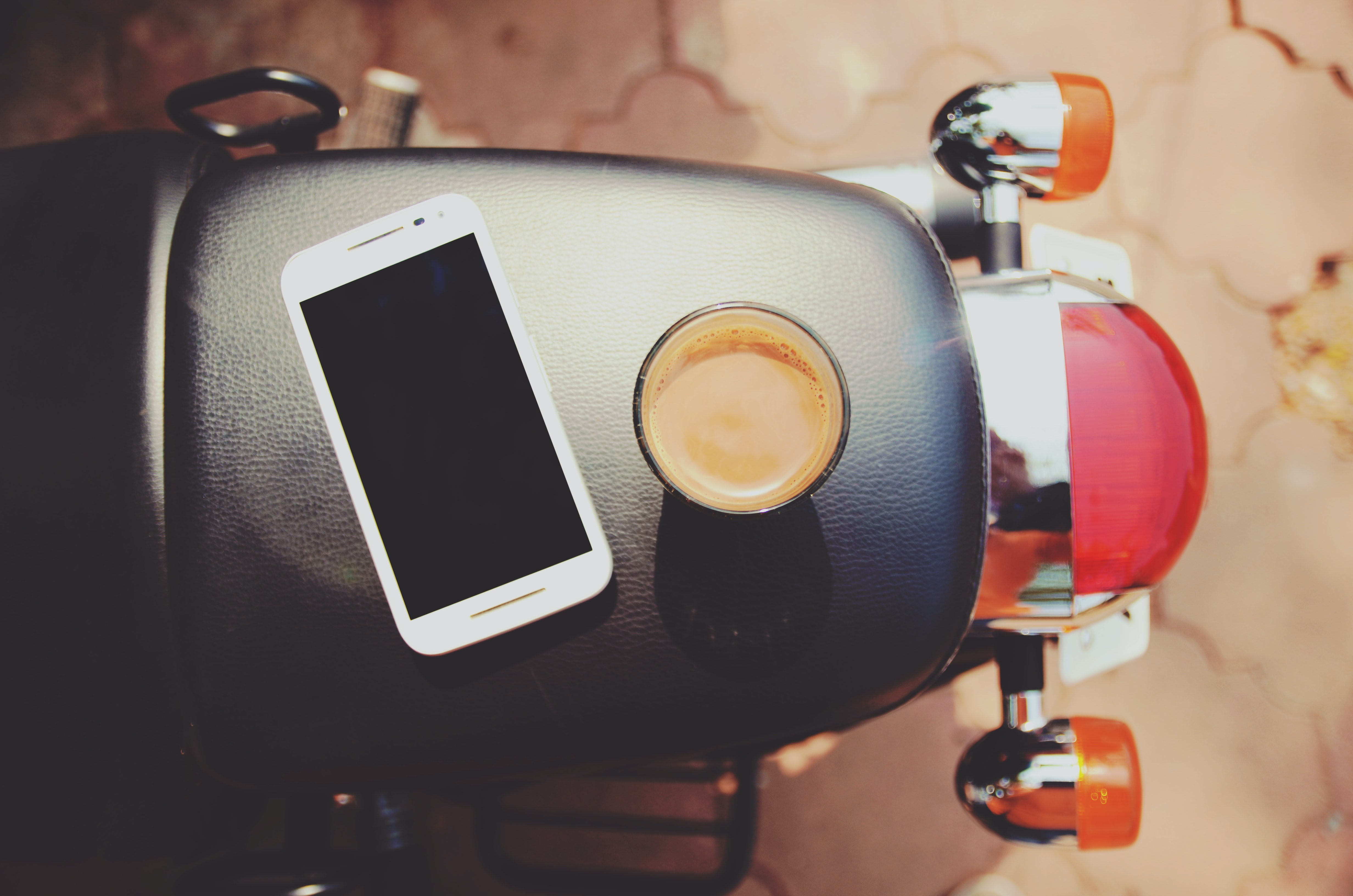 An overhead shot of a smartphone and a cup of coffee on a leather motorcycle seat