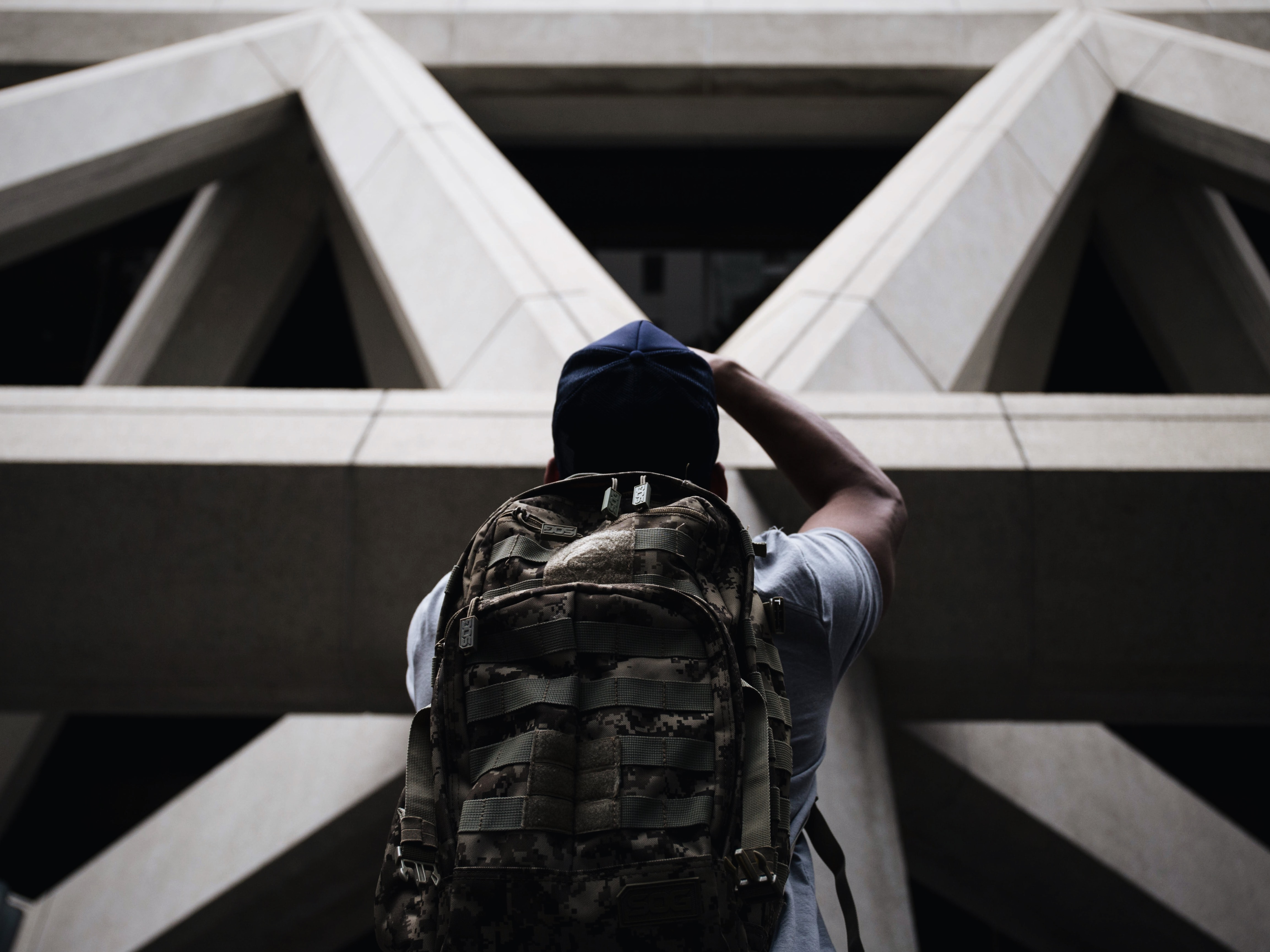 person wearing shirt and hiking bag looking in front of grey concrete structure while standing during daytime