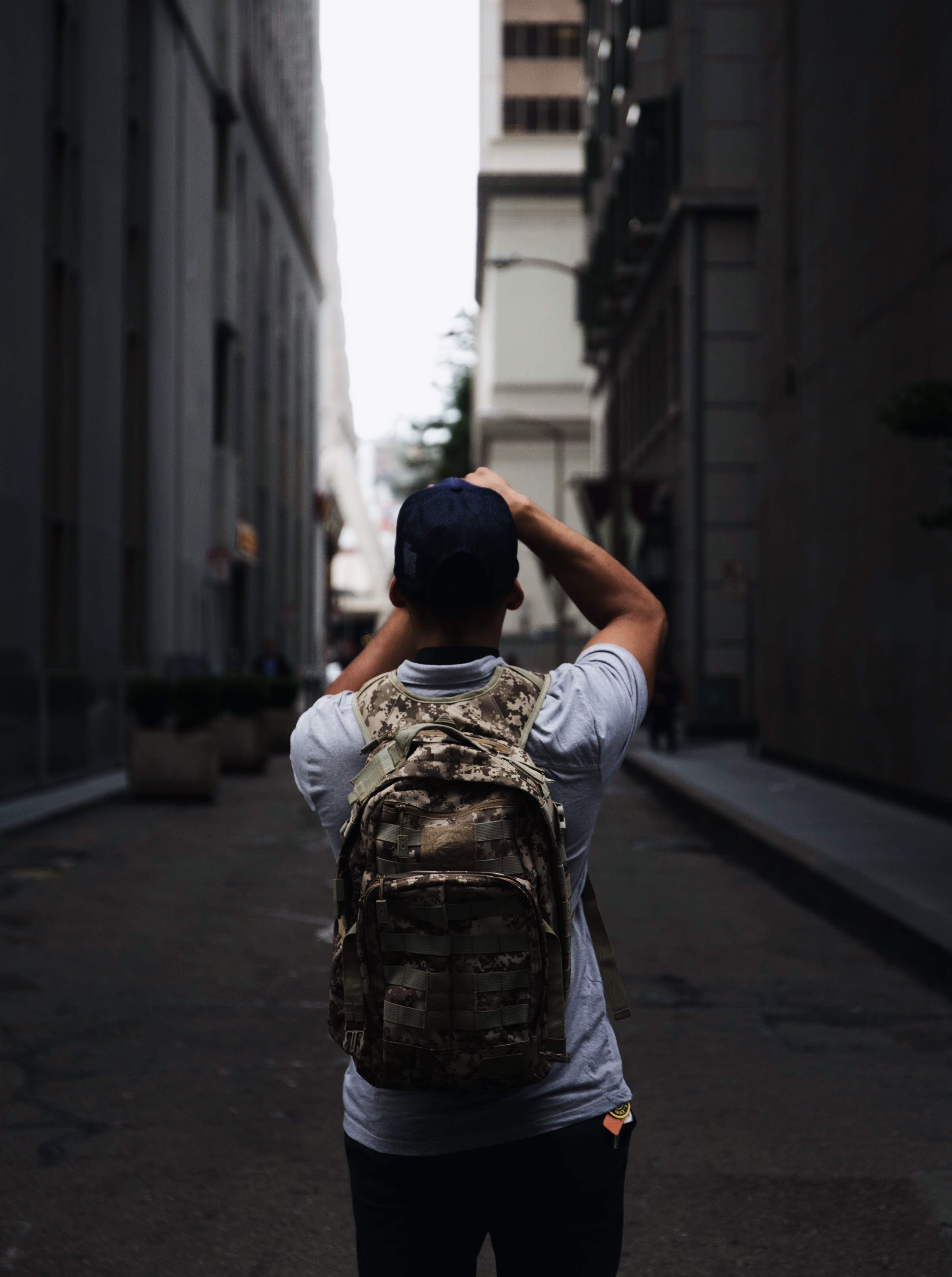 A person in a backpack faces away, pointing a camera down an alleyway