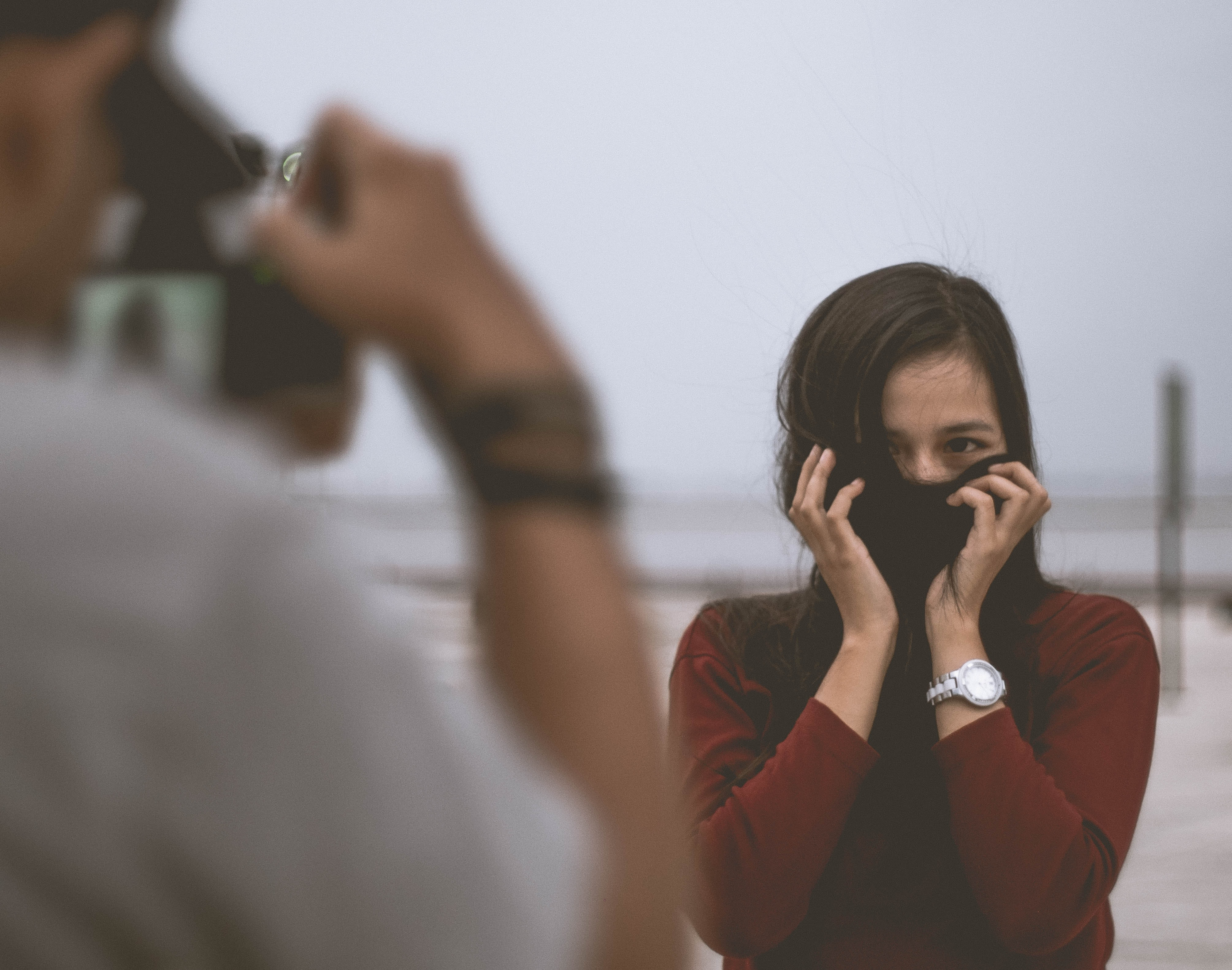 selective focus photography of person wearing white shirt taking photo of woman wearing red long-sleeved shirt covering her face with hair