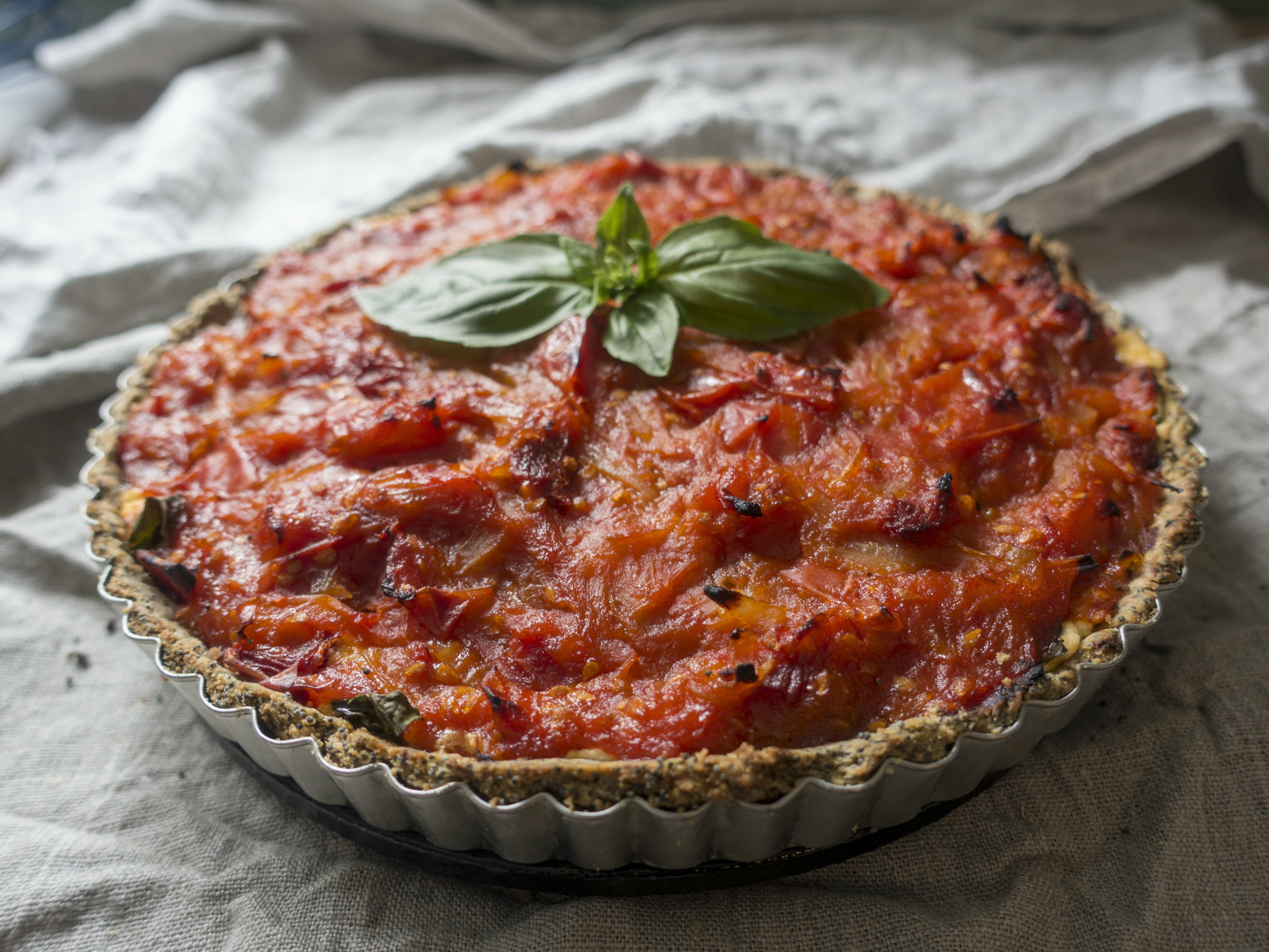 A tart with tomato sauce and basil on top