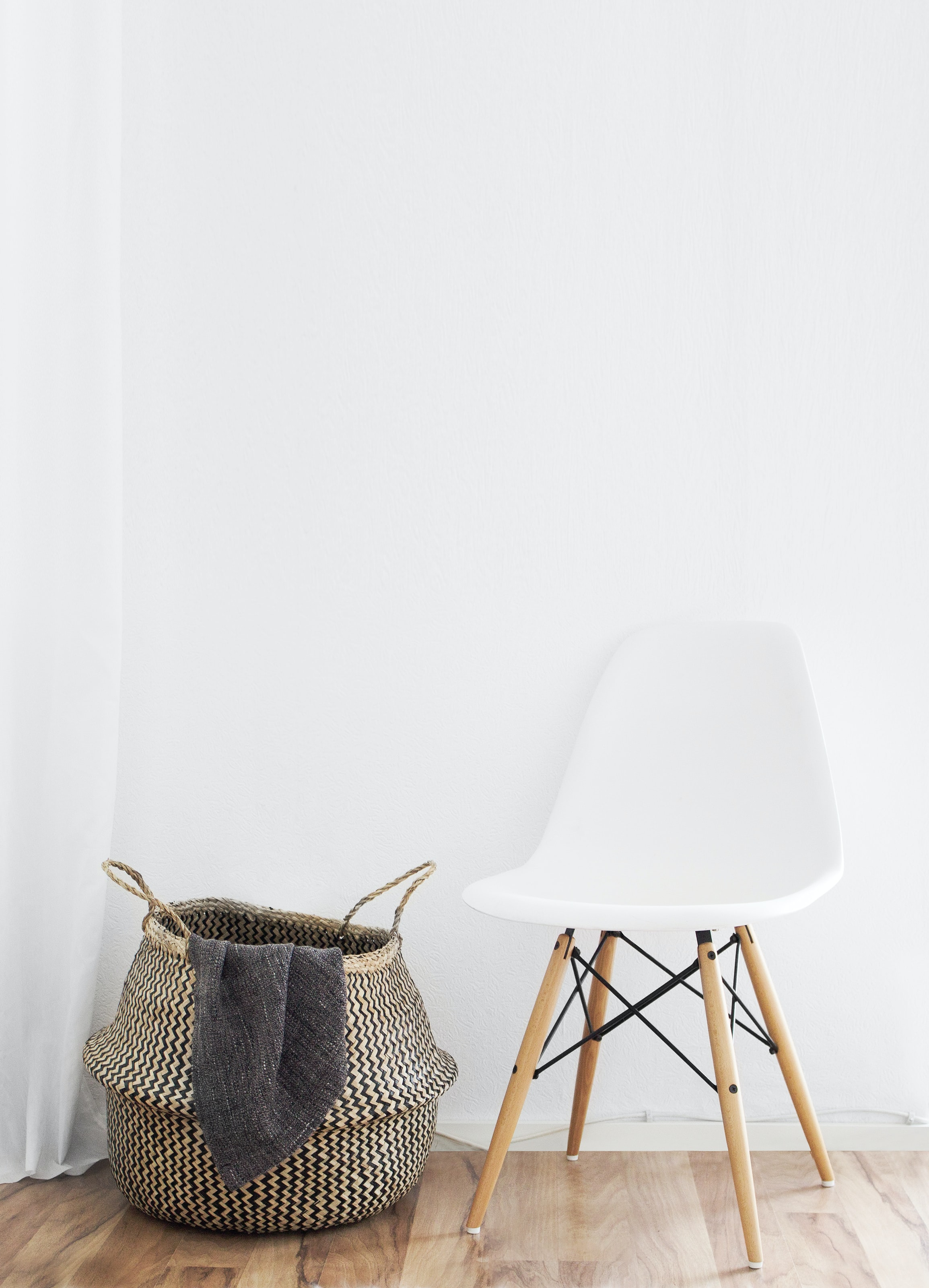 A minimalist shot of a woven laundry basket next to a chair against a white backdrop.