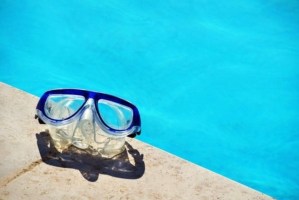 blue framed swimming goggles near pool at daytime