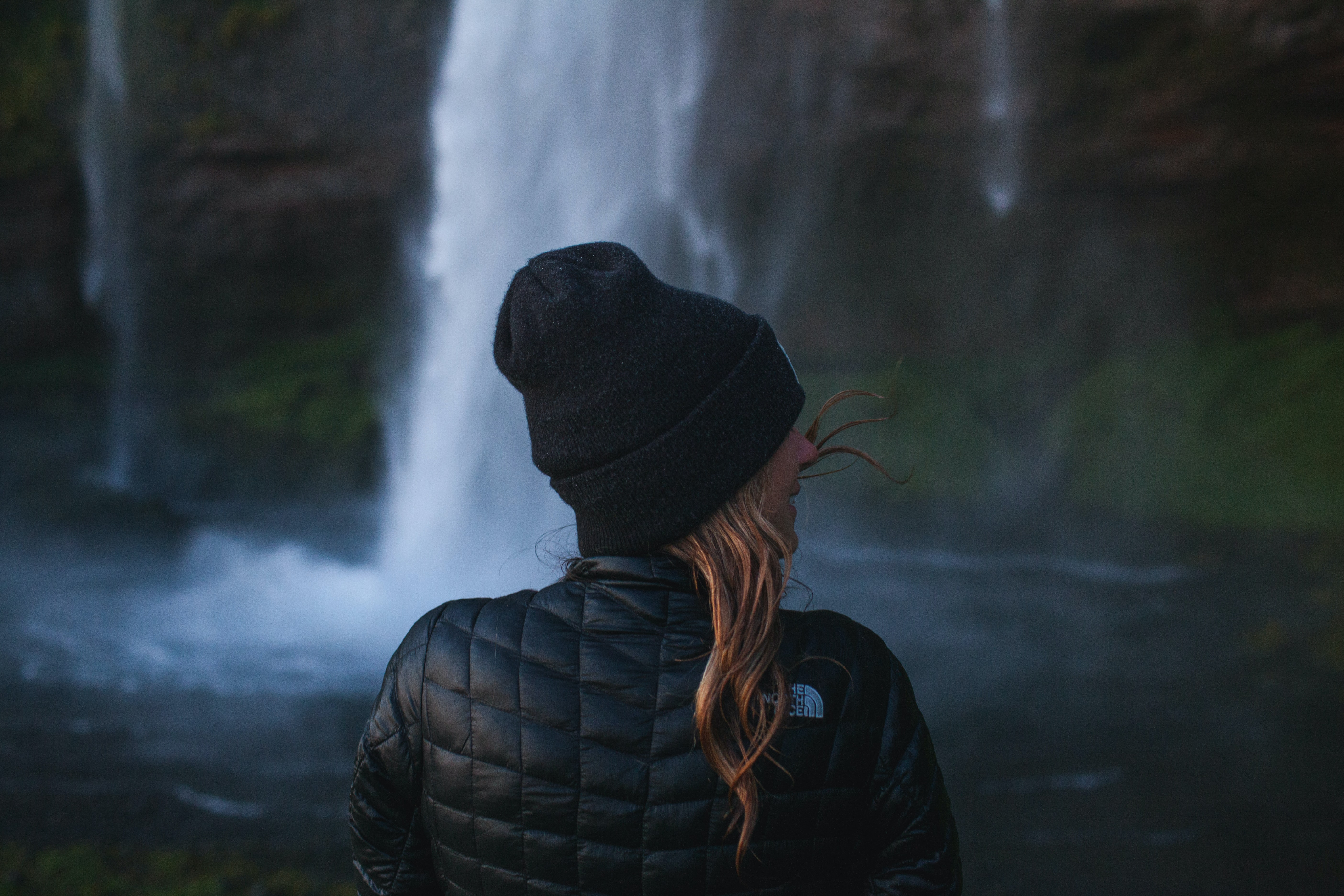 photo of woman wearing black jacket near waterfall