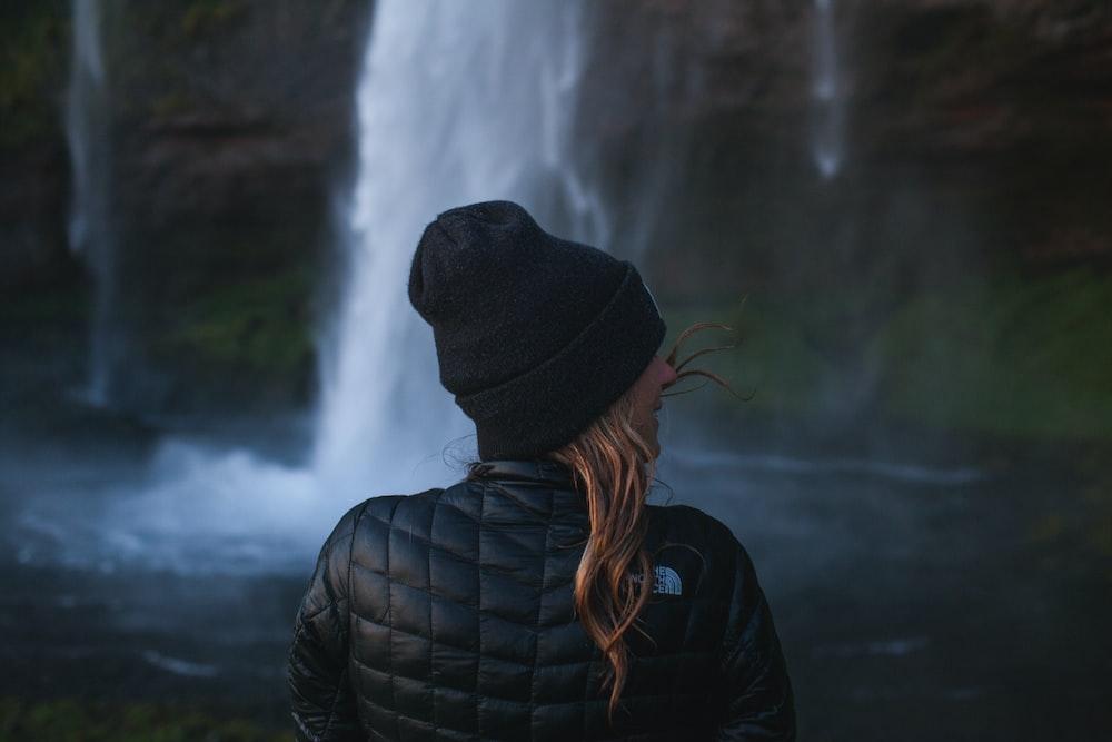photo of woman wearing black jacket near waterfall