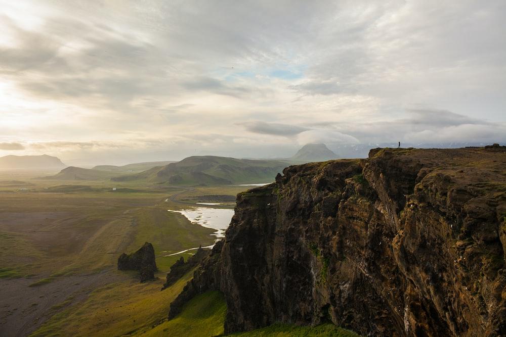 rocky cliff facing green grass fields
